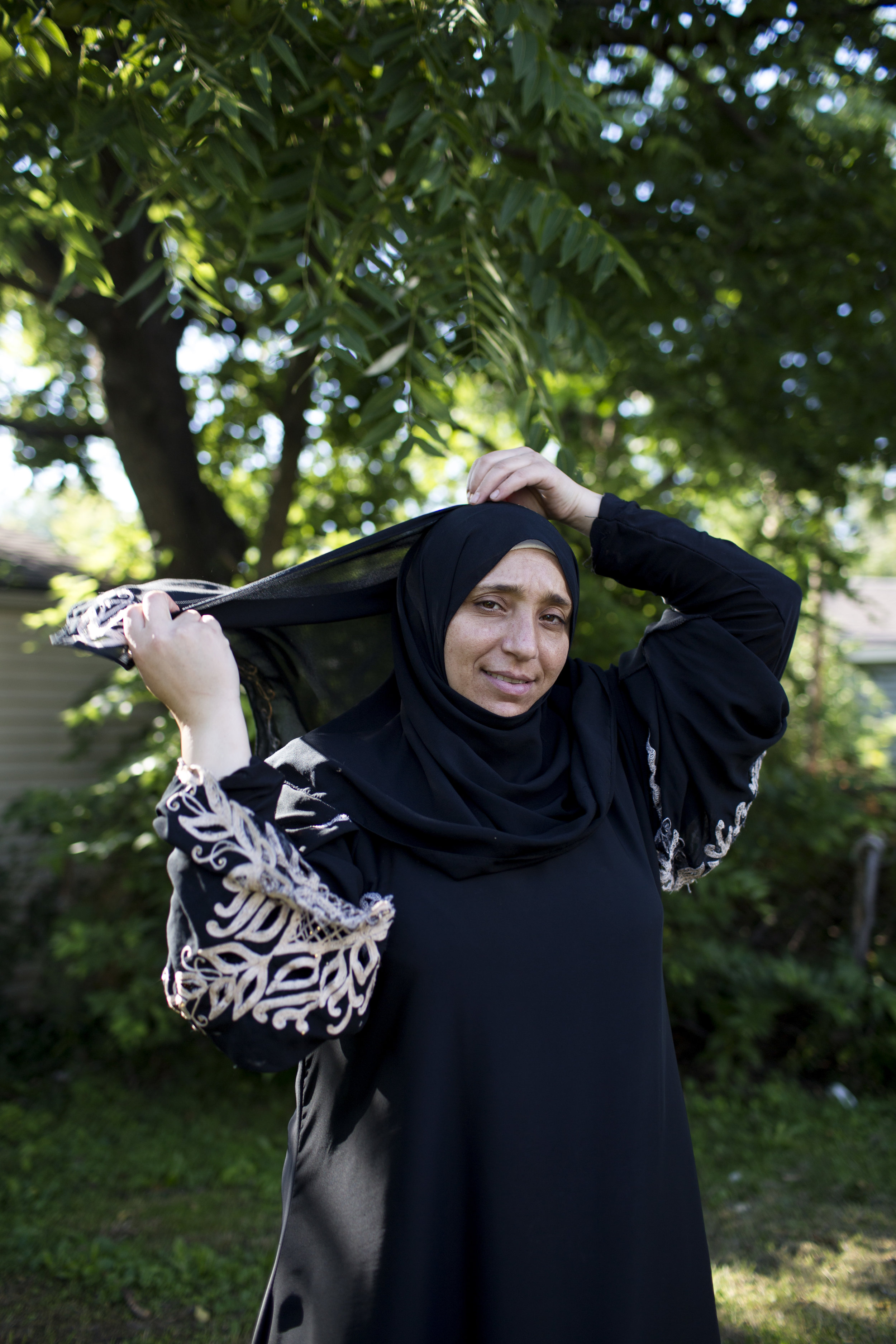 Mariam adjusts her hijab for a portrait in her backyard.