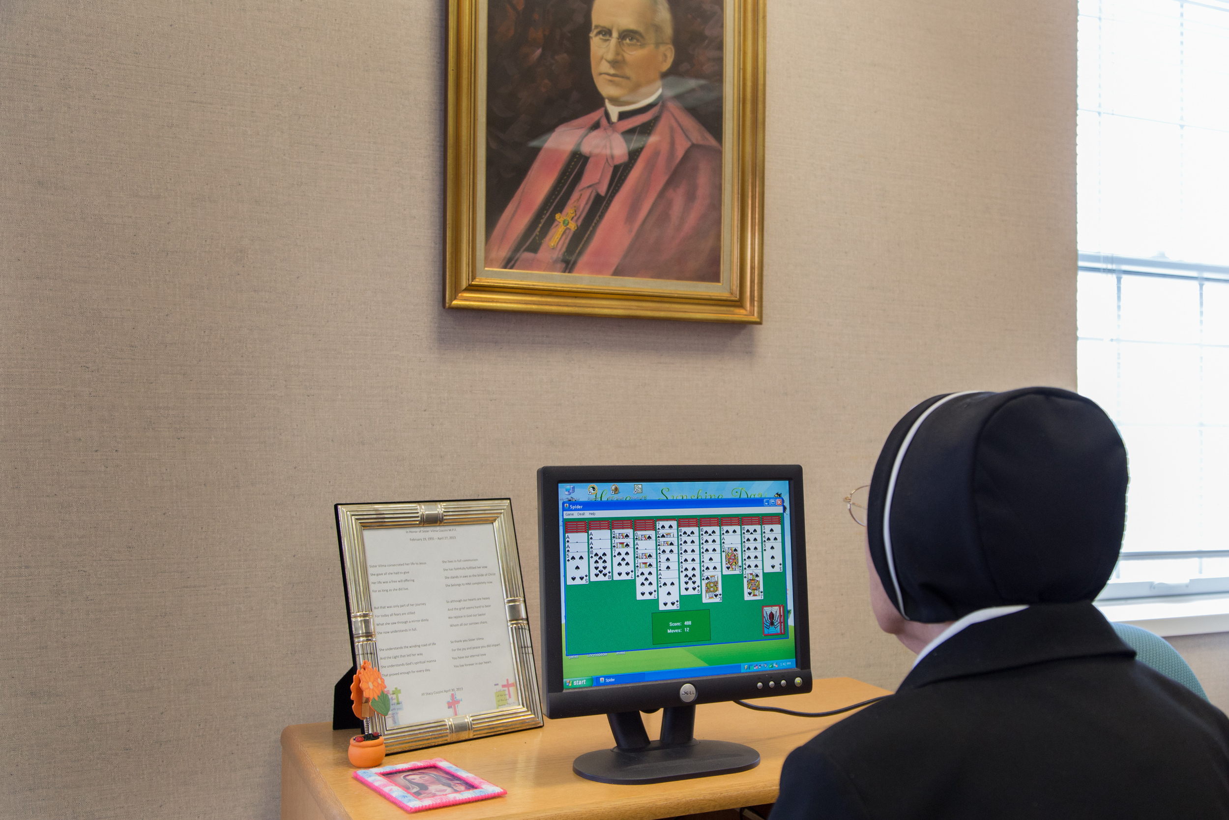 A Sister who works in the infirmary library, takes time out of her day to play an on-line game of Black Widow Solitaire.