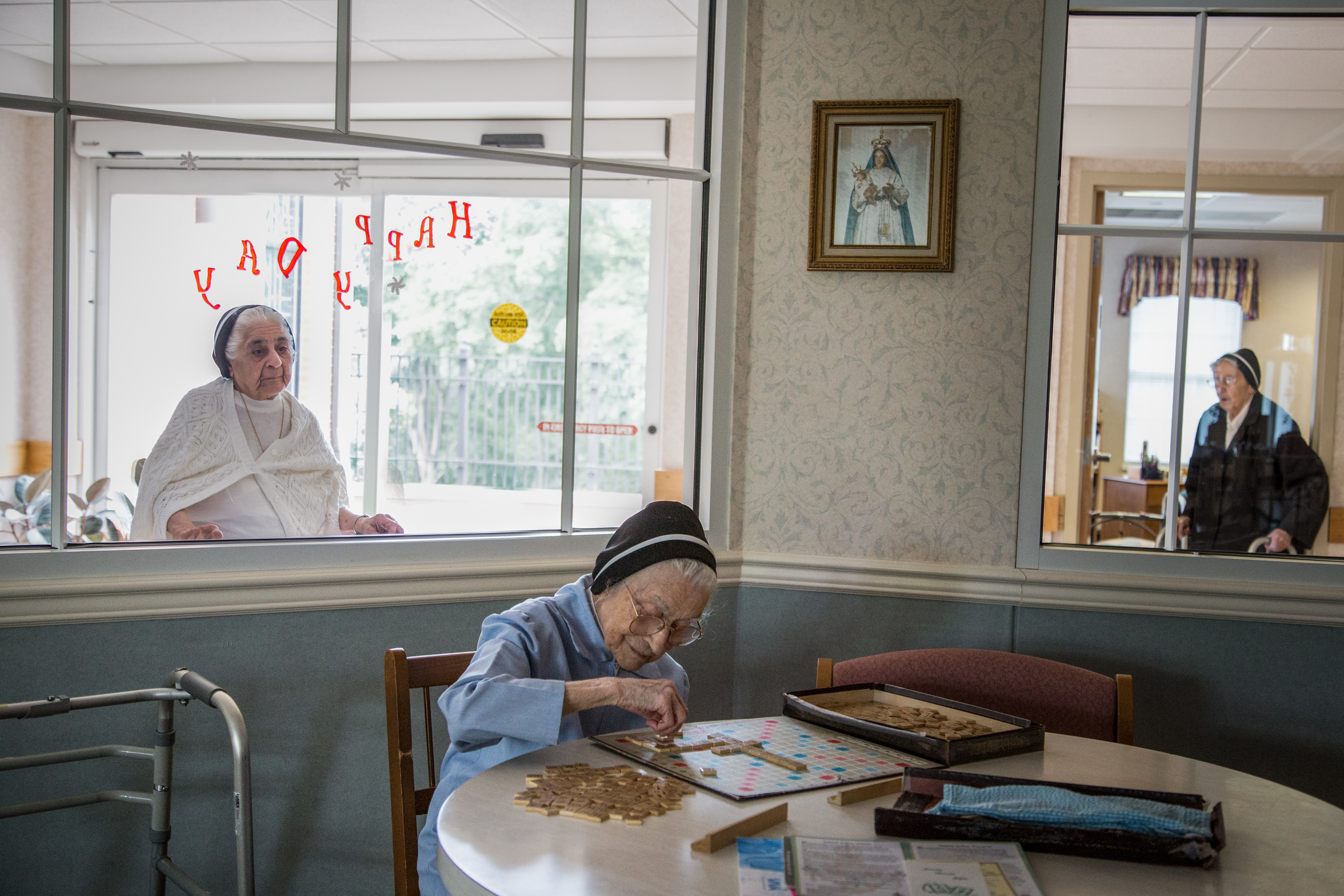 At 100 years of age, Sr. Mary Testa enjoys playing Scrabble every day in the Infirmary's Community Room. The scattered tiles spell words related to teaching such as: schools, teachers, pupils, books, girls, boys, and years.