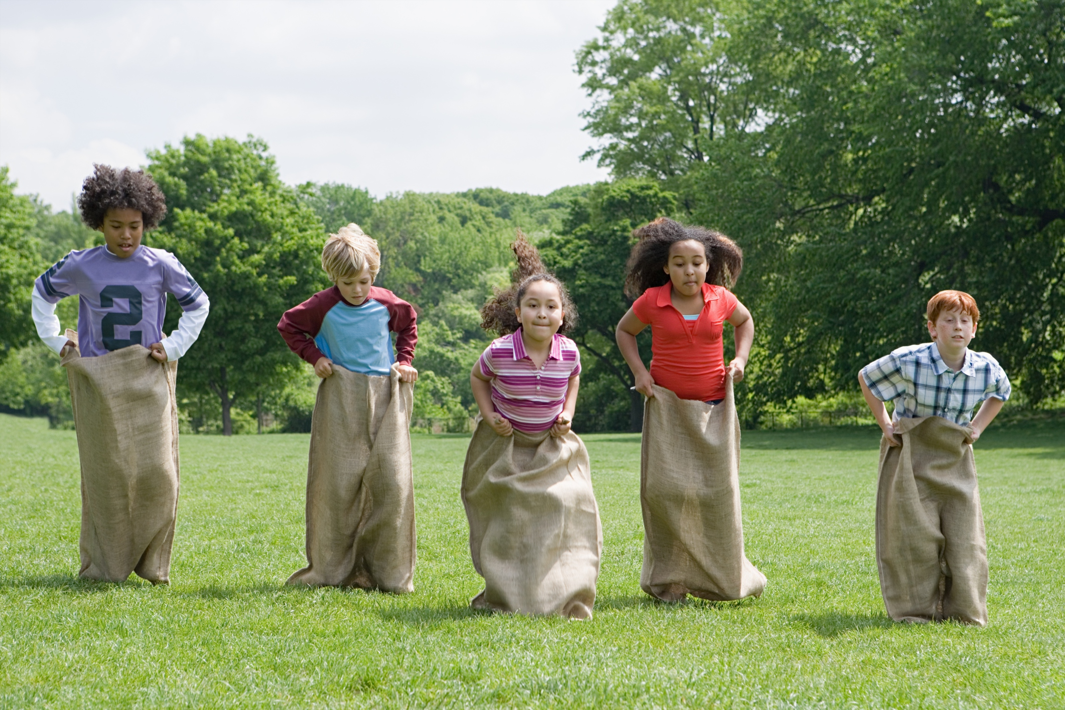 Group of kids playing a potato sack race game at a children's event.