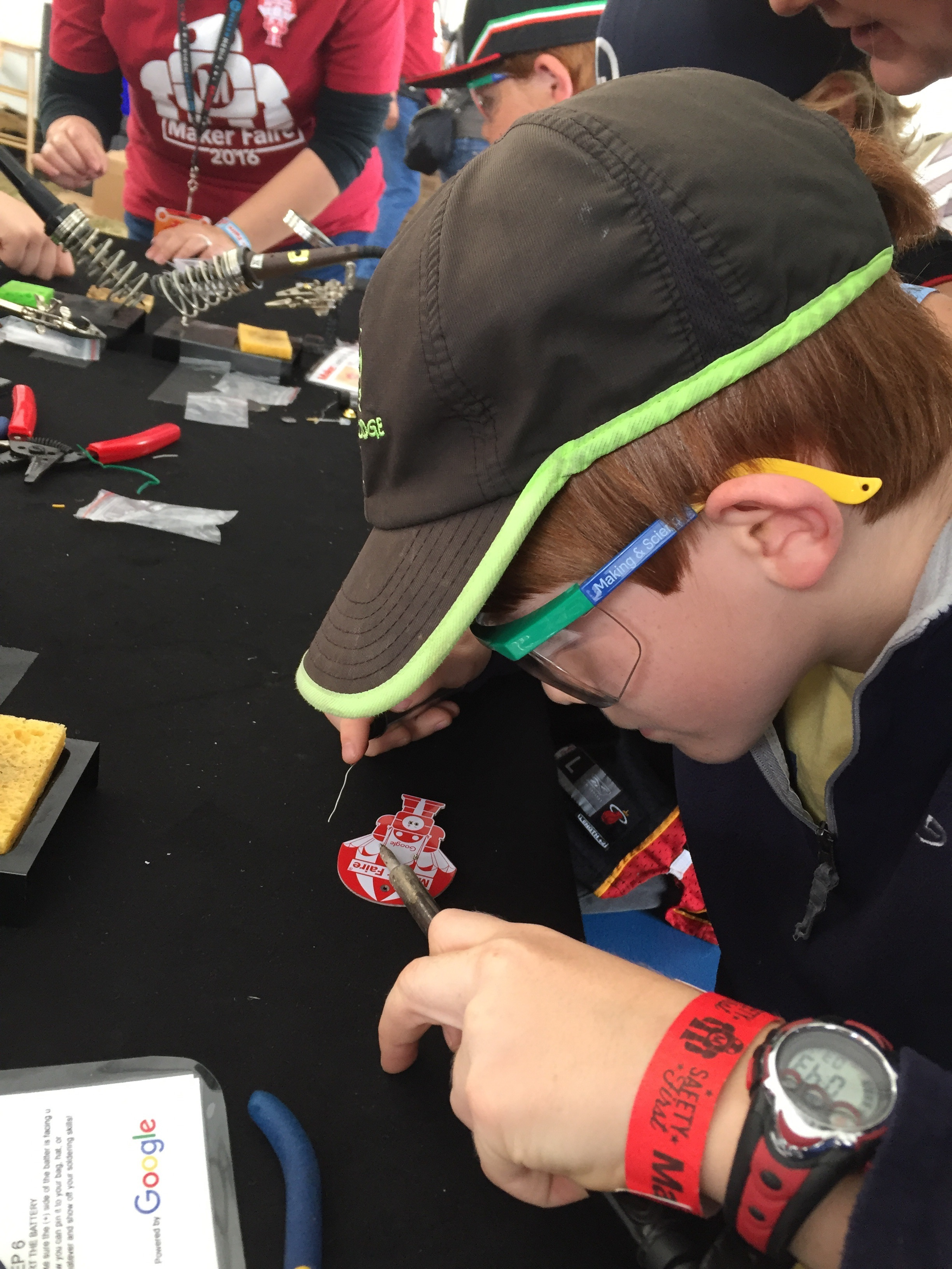Learning to solder at MakerFaire