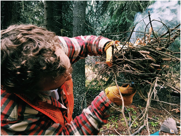 Henry working on lighting his twig bundle, where the thinnest branches and other dry material are concentrated in the middle