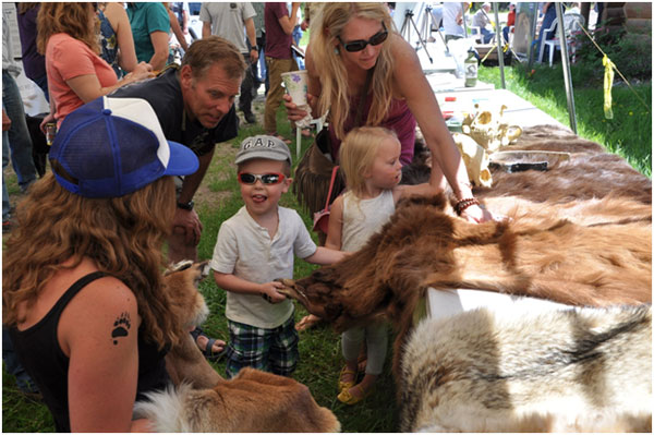 Youngsters checking out bear hides at the Bear Fair