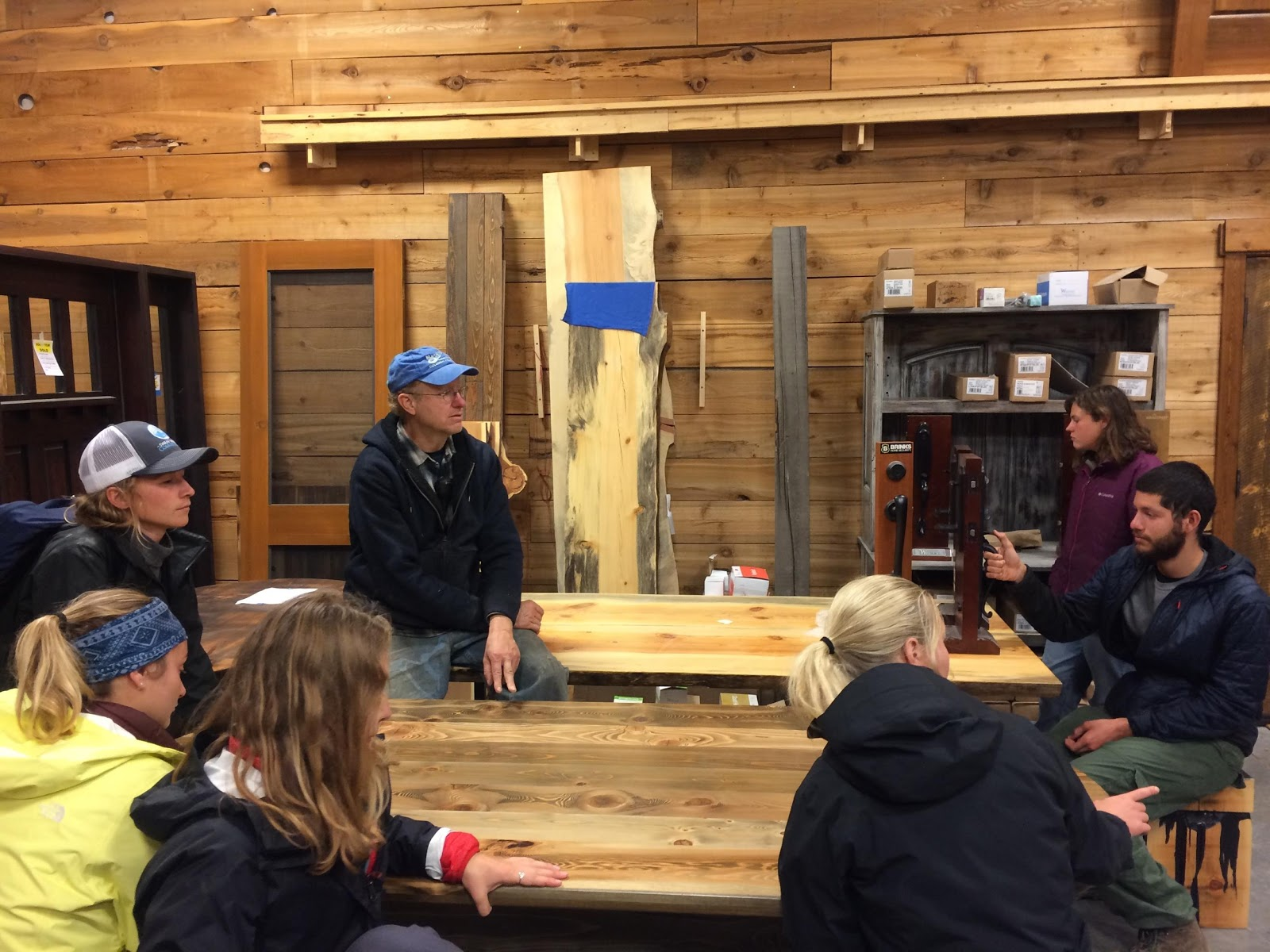 Seated around hand crafted tables made in the door shop at RBM, students listened to Ben Thompson discuss RBM's practices and efforts to reduce waste at the mill. Photo by Meredith Fraser.