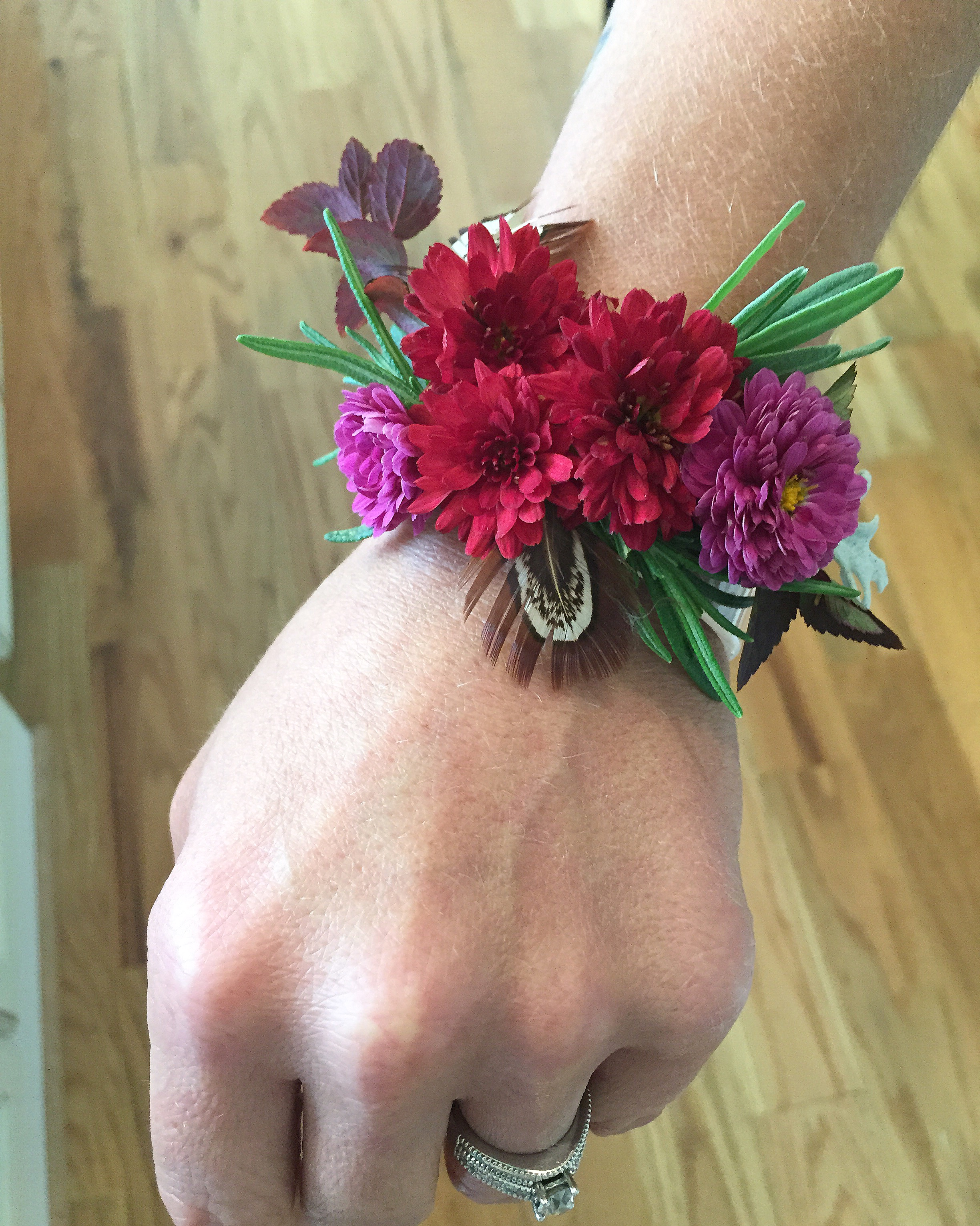 Floral bracelet designed by Westvirjeni with mums, rosemary, spirea, and grouse feathers.