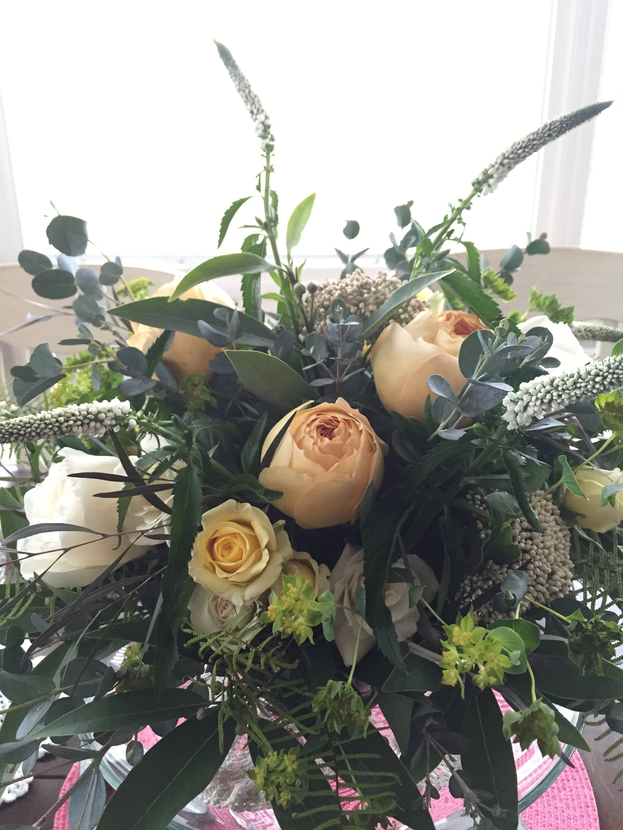 Floral design by Westvirjeni in a white and yellow color scheme in a silver nesting bowl.