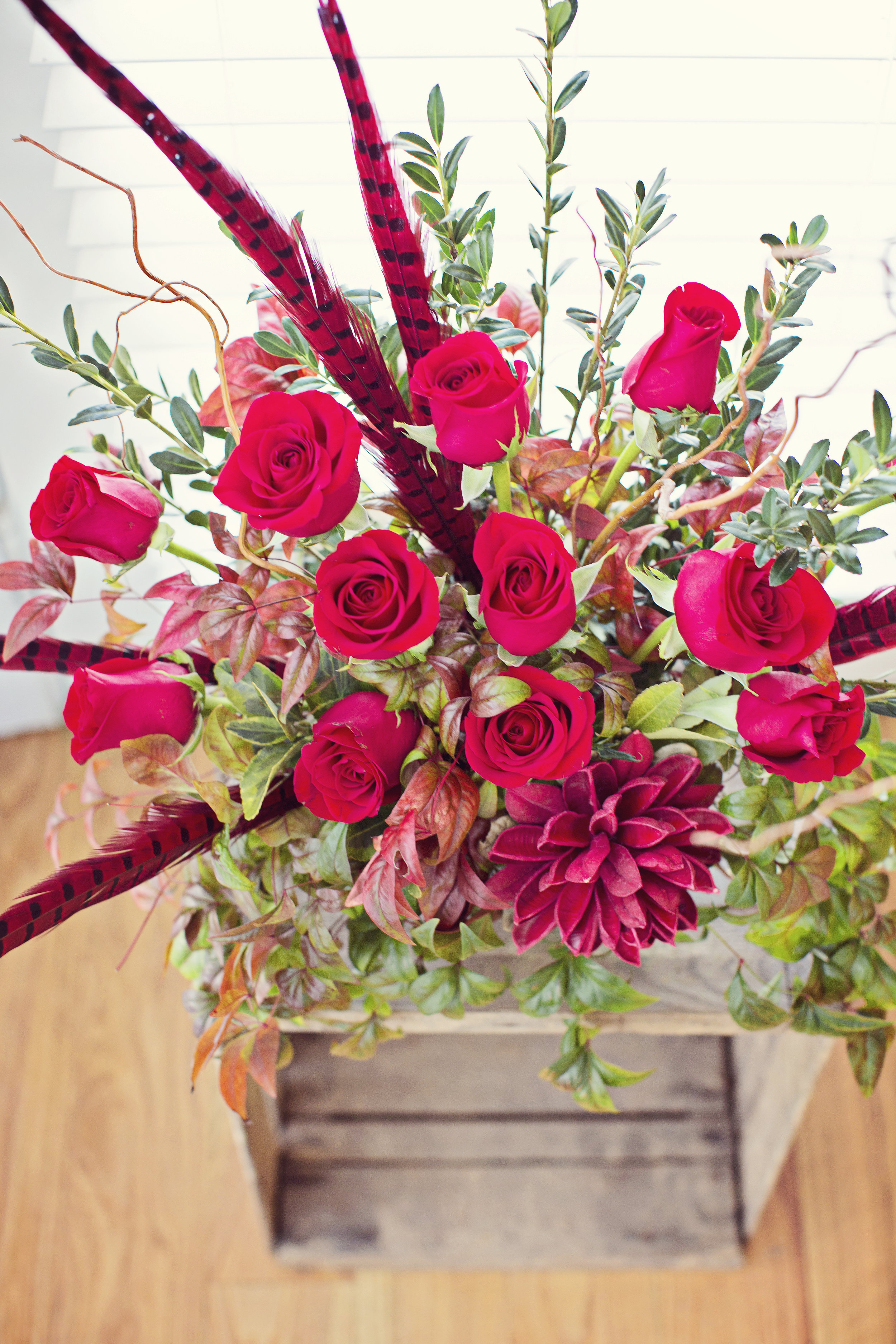 Woodland Roses $95   One dozen red roses with mixed greenery and wintery, woodland accents.