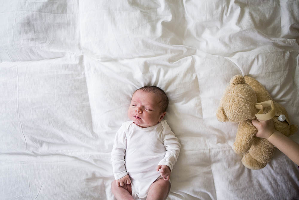 Big sister shows newborn brother a teddy bear