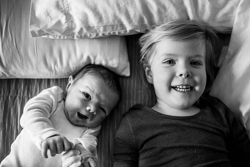 Connecticut family photography in black and white with siblings laying together