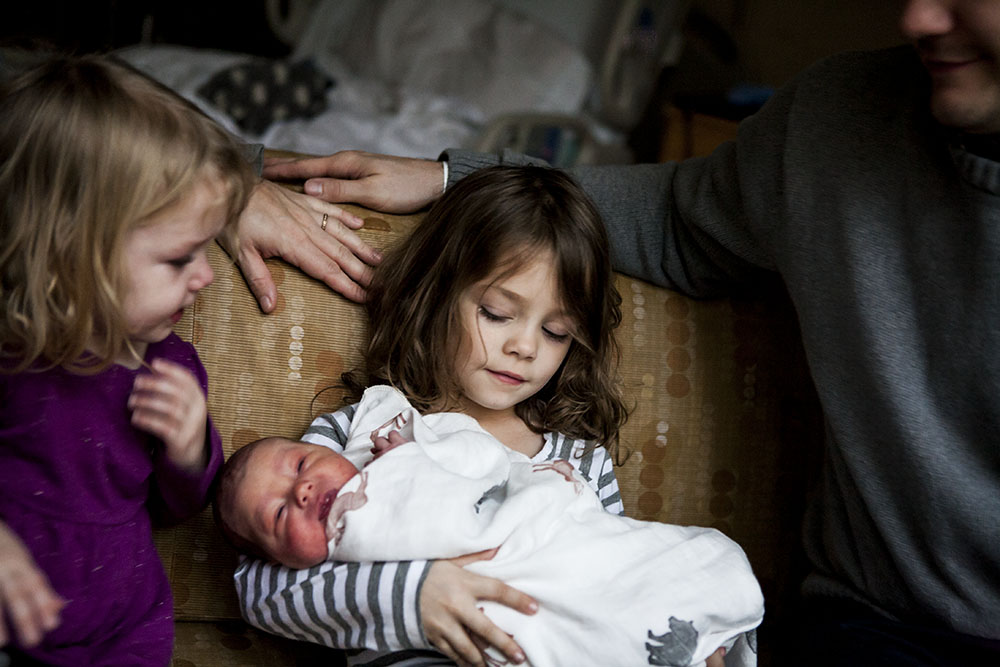 Sisters meet their newborn baby brother.