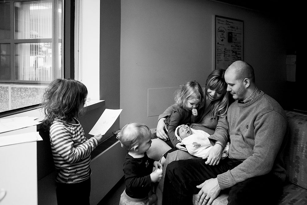 Family of four say hello to newborn baby, oldest sister reads baby a birthday card.
