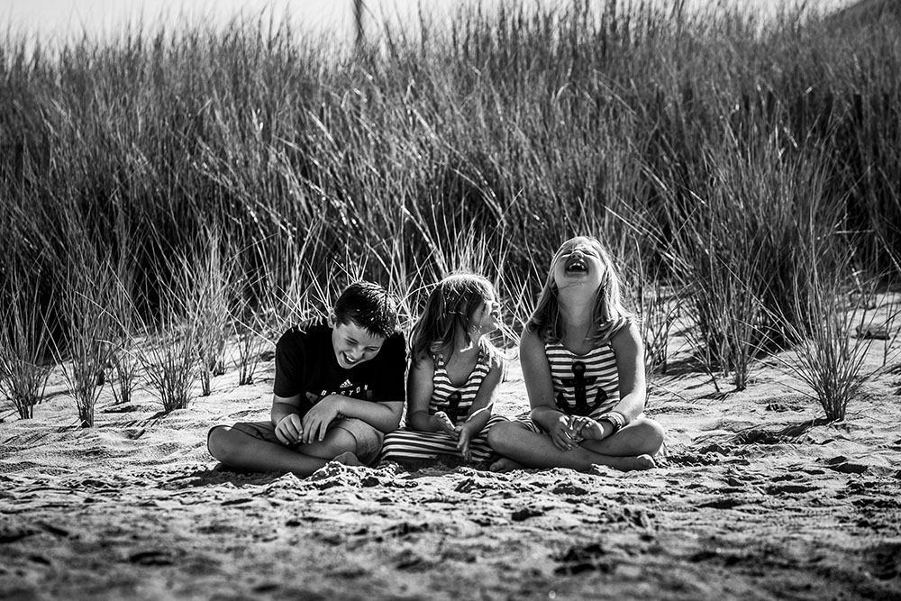 Candid black and white photography featuring siblings at the beach in Rhode island with sand and grass and the children are laughing.