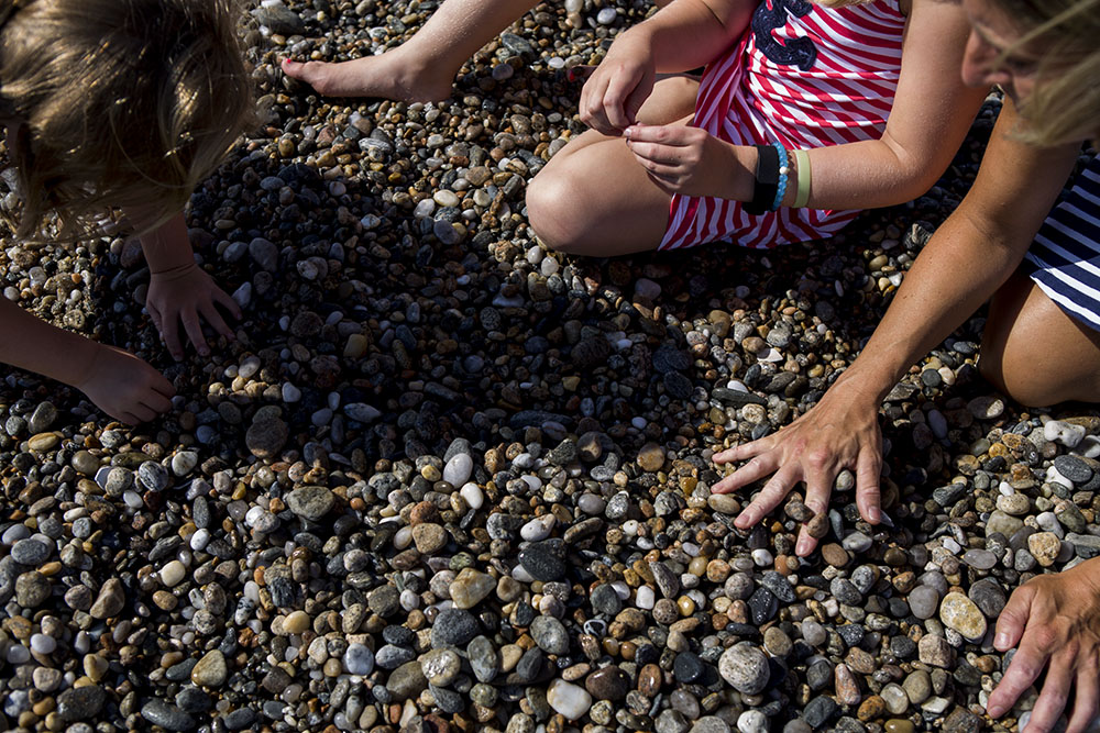 Mother and two daughters hands sort through a pile of pebbles looking for sea glass in this pictures by documentary family photographer Chelsea Silbereis