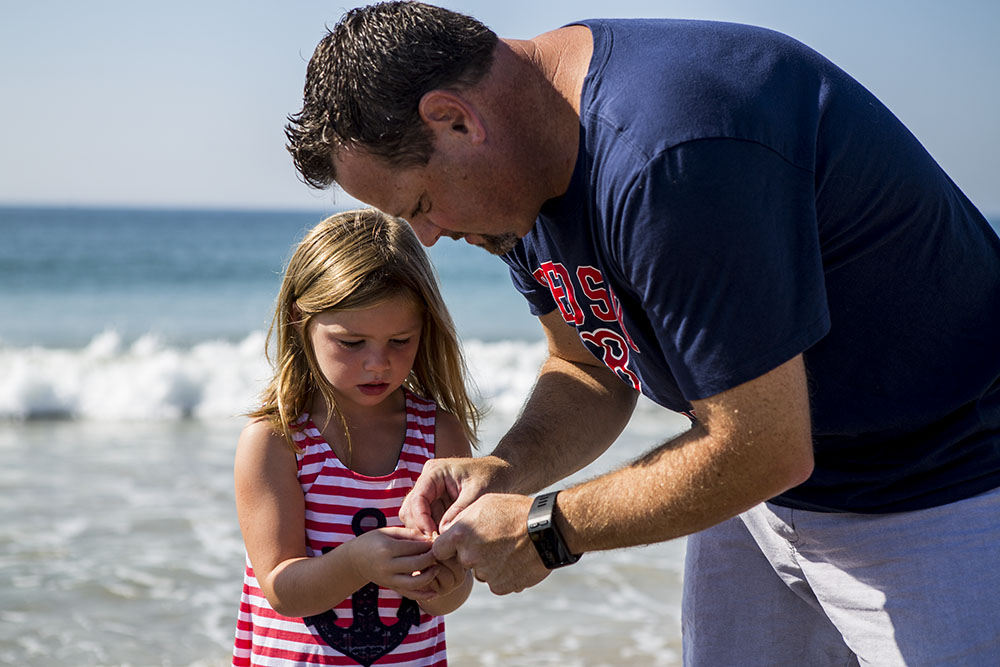 Documentary family photography featuring a father and daughter on a beach in Rhode Island looking at a piece of sea glass with a breaking wave in the background.