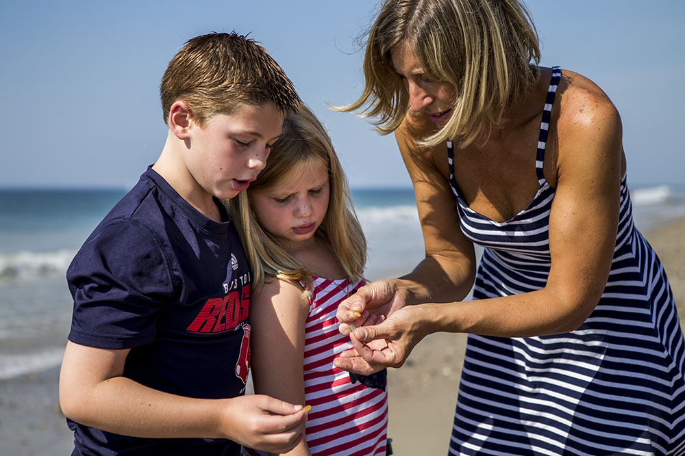 Beach photographer Chelsea Silbereis creates family pictures of mother showing her son and daughter a piece of sea glass on a Rhode Island beach with the shoreline and ocean behind them.