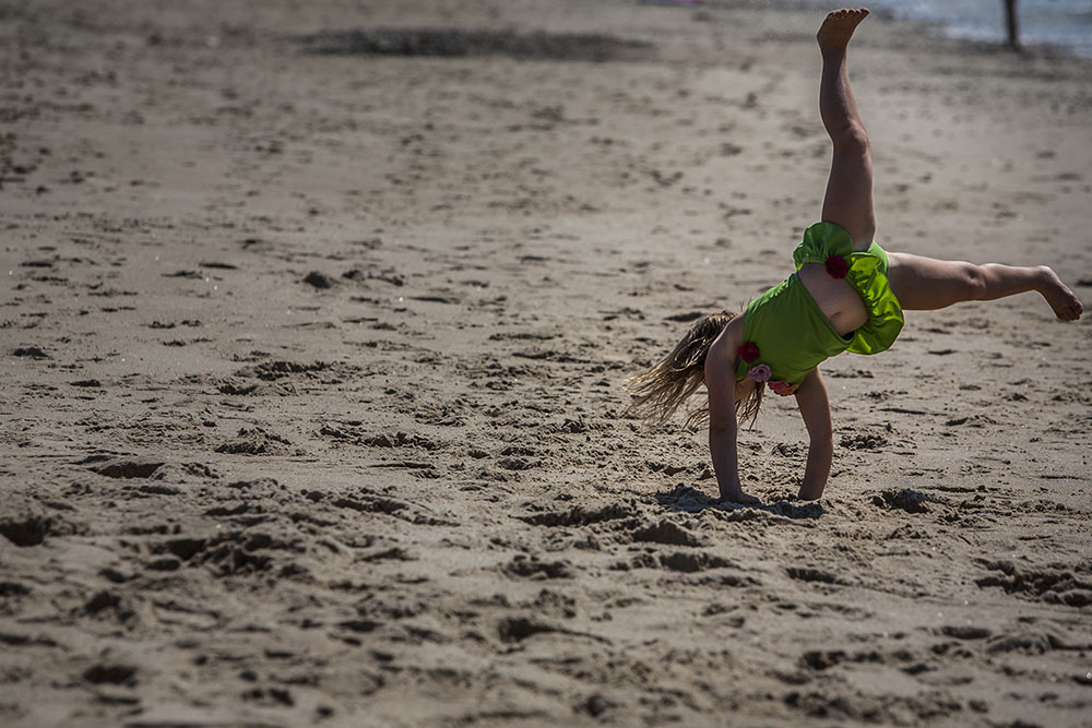 Connecticut shoreline family photographer, Chelsea Silbereis, captures this childhood beach portrait of a girl in a green swim suit doing a cartwheel on the sand.