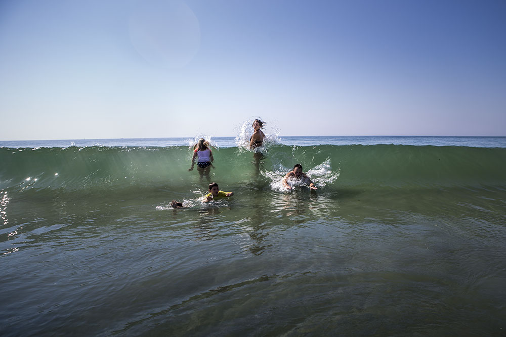 Rhode Island beach photography featuring a family body surfing a wave.