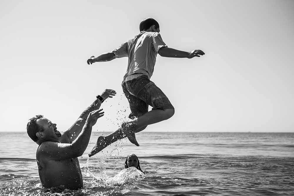 Family photojournalism featuring Connecticut father throwing his son into the ocean over daughter's head, the beach is in Rhode Island.