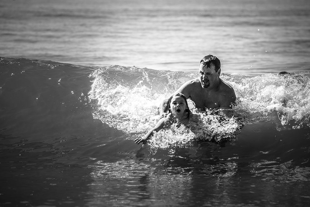 Father helps daughter body surf on a Rhode Island beach in this black and white pictures by Chelsea Silbereis Family photography.