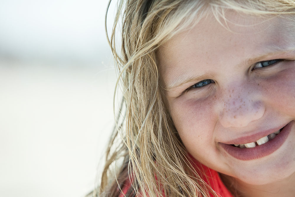 Close up portrait of blonde girl with blues eyes at the beach by authentic kid photographer Chelsea Silbereis serving New York and Fairfield County Connecticut.