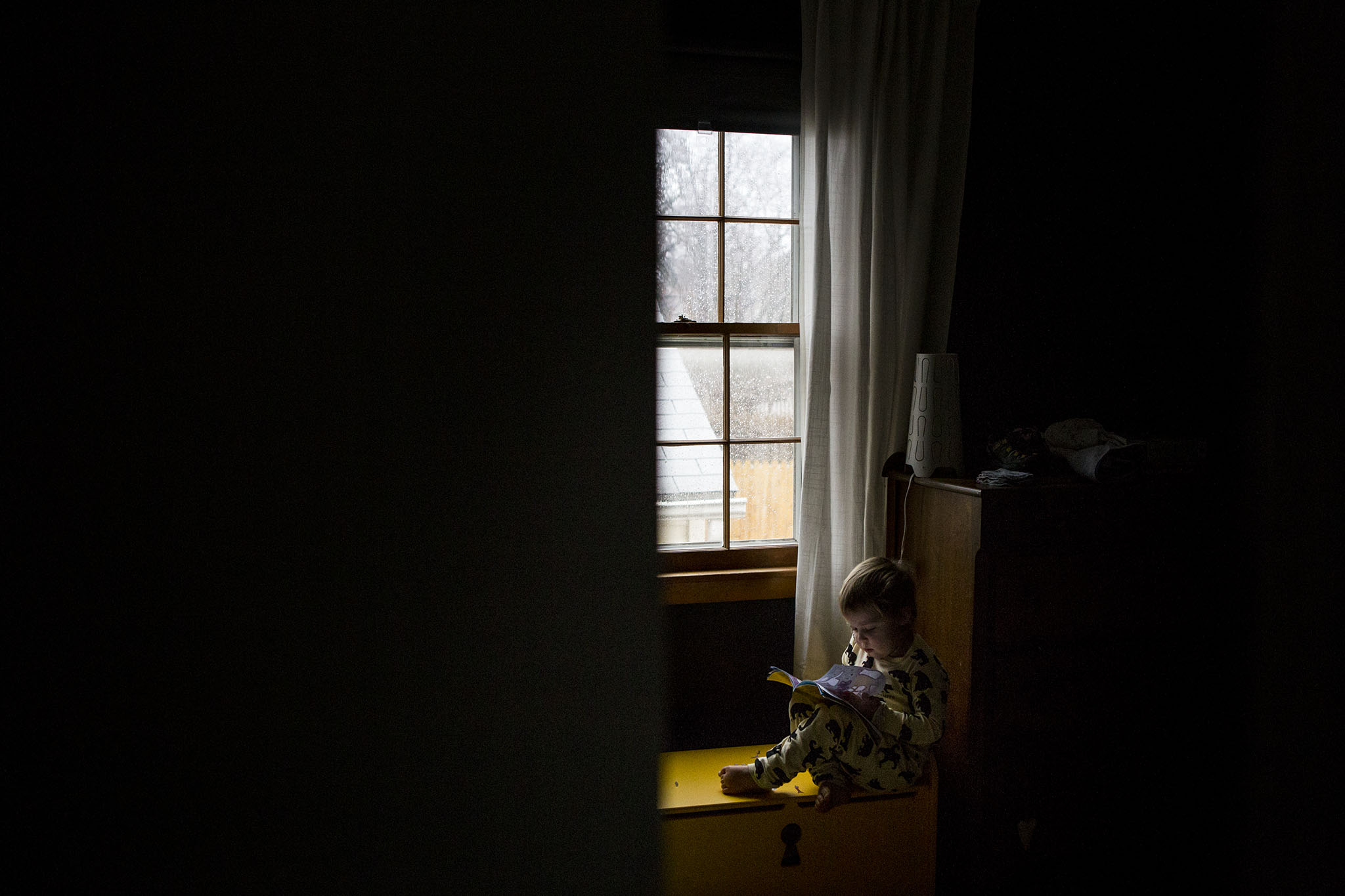 Lifestyle family photography in Connecticut with toddler girl reading in a window.