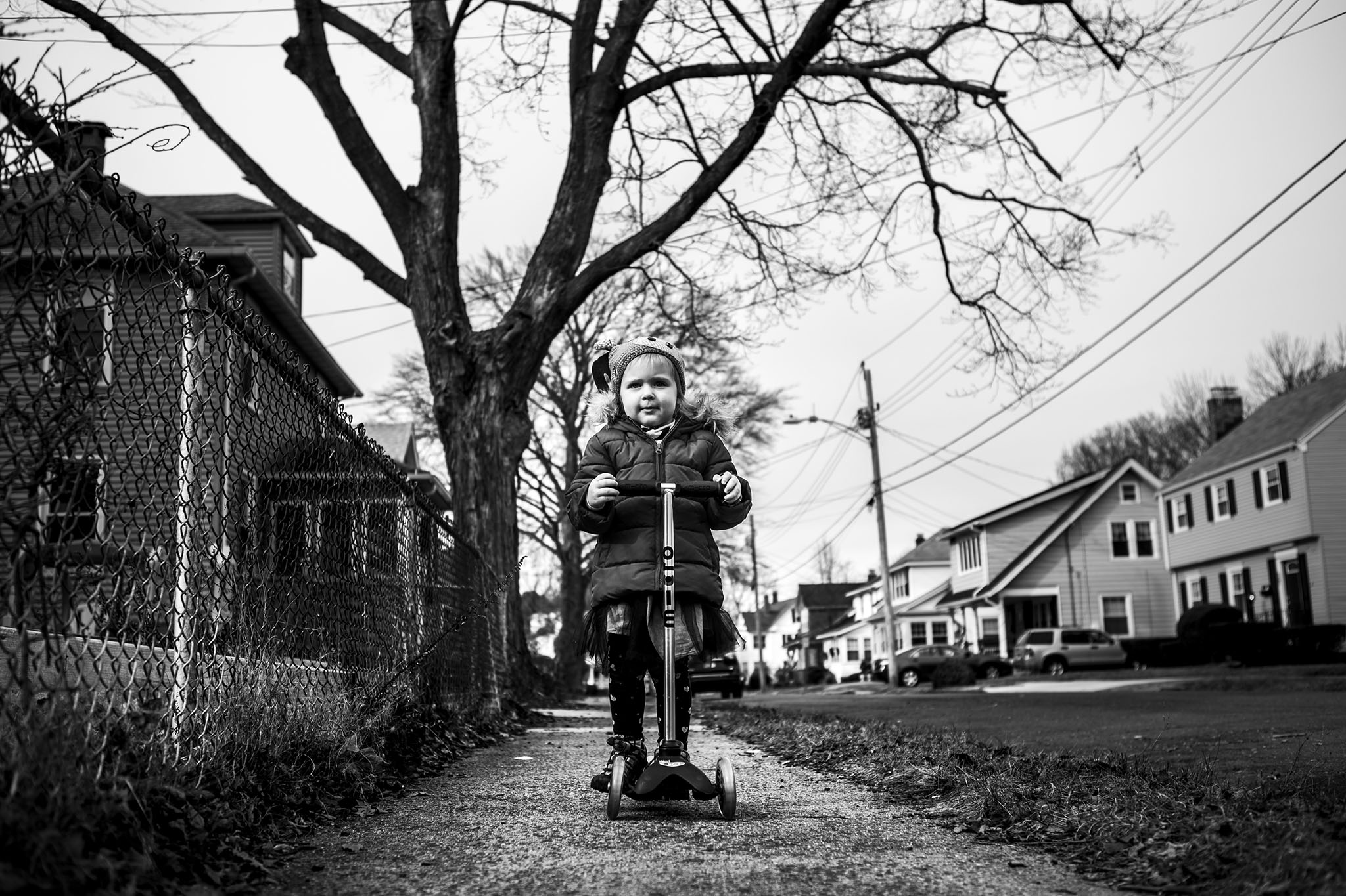 Best Connecticut Family photographers make candid lifestyle and documentary pictures in black and white of kids playing with scooters.