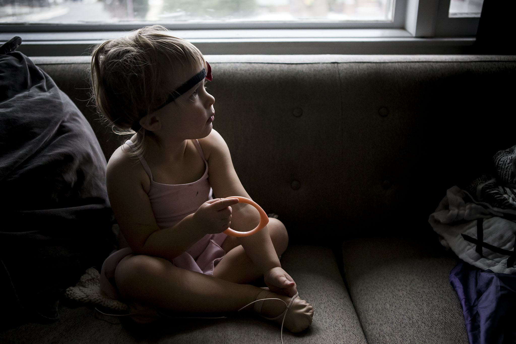 ct family photographers image of toddler in ballet clothes sitting on couch.