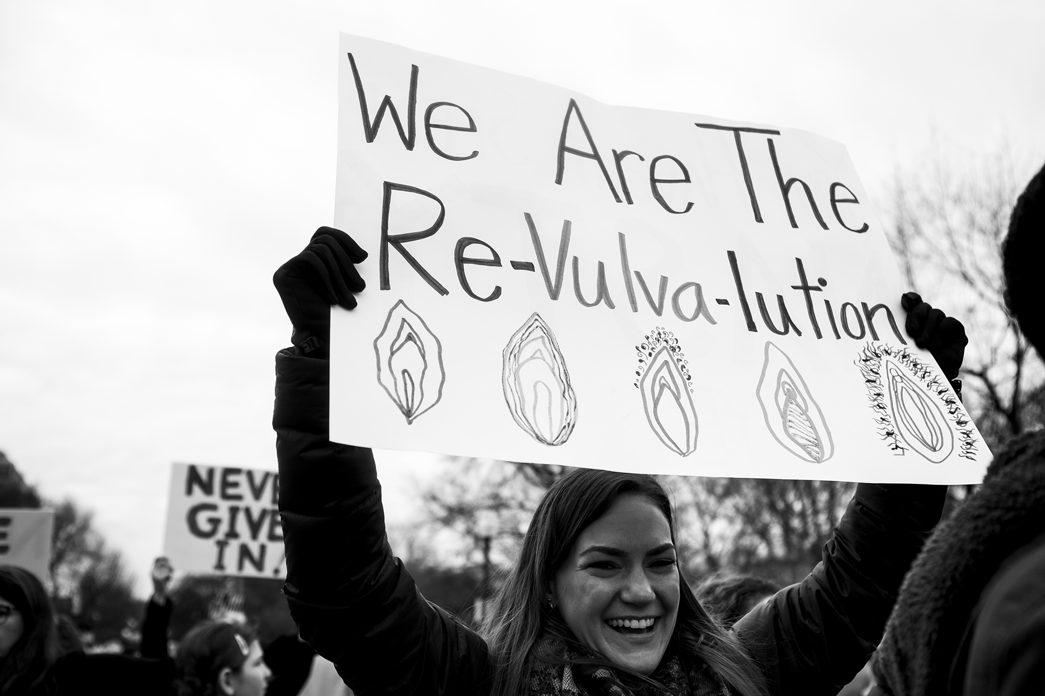 """Smiling woman holding protest sign """"we are the revulvalution"""" at the women's march on washington sister march in boston."""