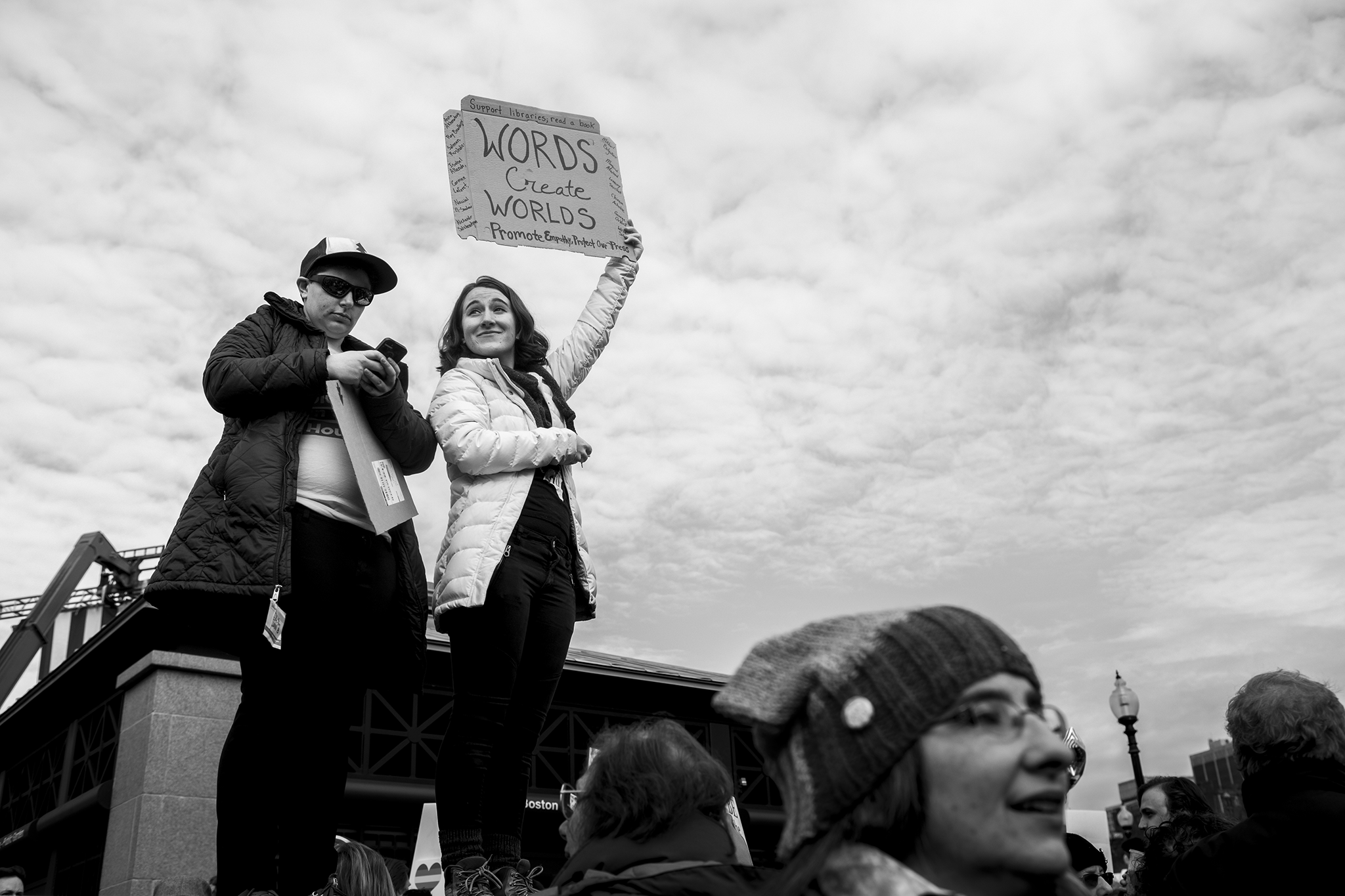 """two women stand above the crowd at the women's march on washington sister march in boston. One is holding a protest sign that reads """"words create worlds"""" the other is using her smart phone."""