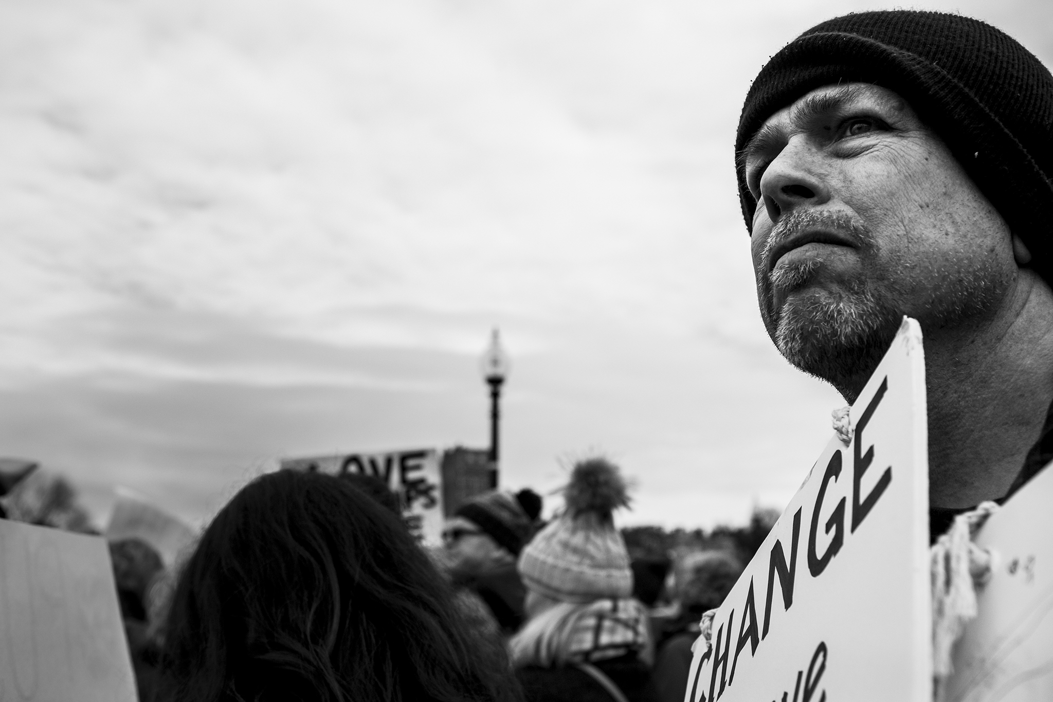 """father supporting daughter and women at march on washington sister march boston holding a sign that says """"change"""""""