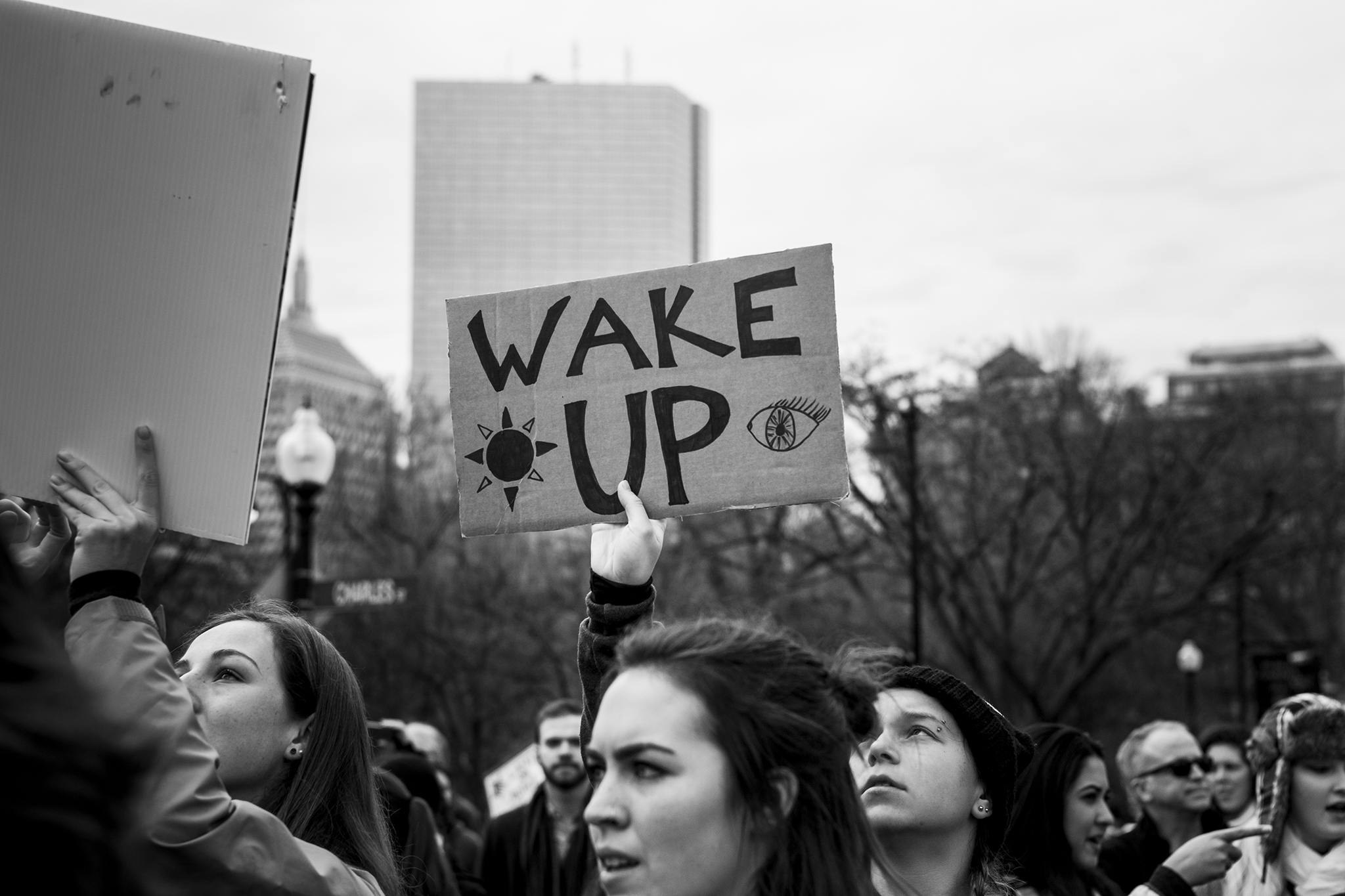 """young women protesting at the women's march on washington sister march in boston, sign reads """"wake up"""""""