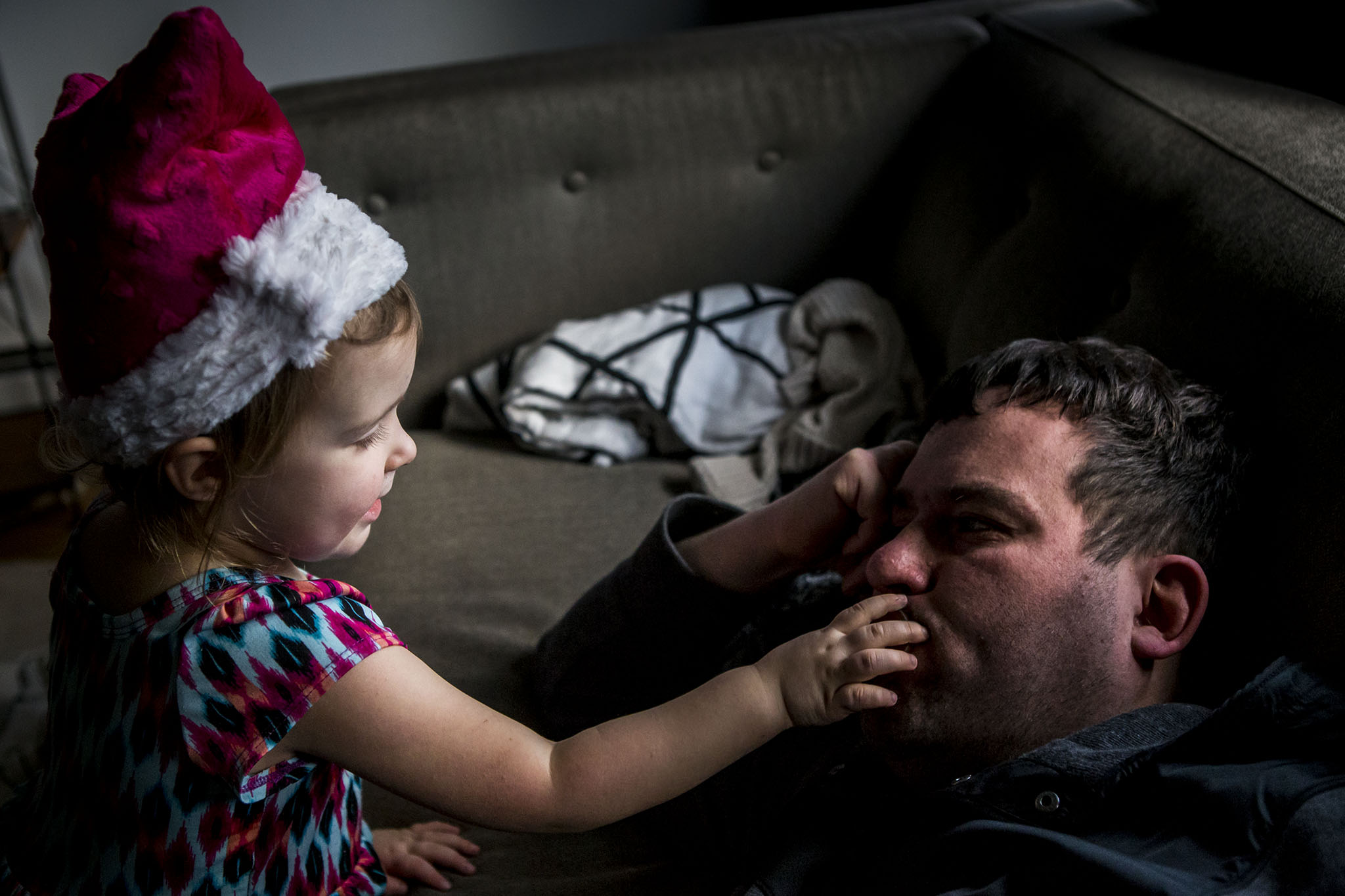 daughter touches father's mouth in candid ct portraiture.