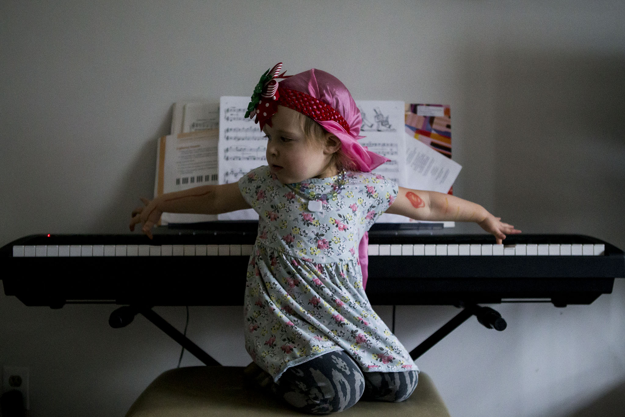 Toddler plays piano backwards while wearing a pink headscarf with a headband in a funny connecticut kid portrait.