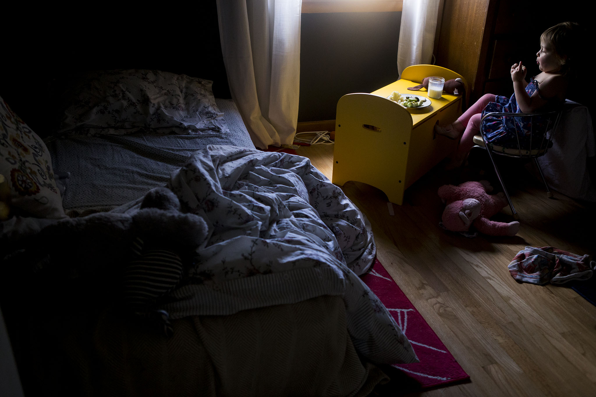 Toddler eats lunch in her bedroom in fine art toddler portraiture with dramatic light