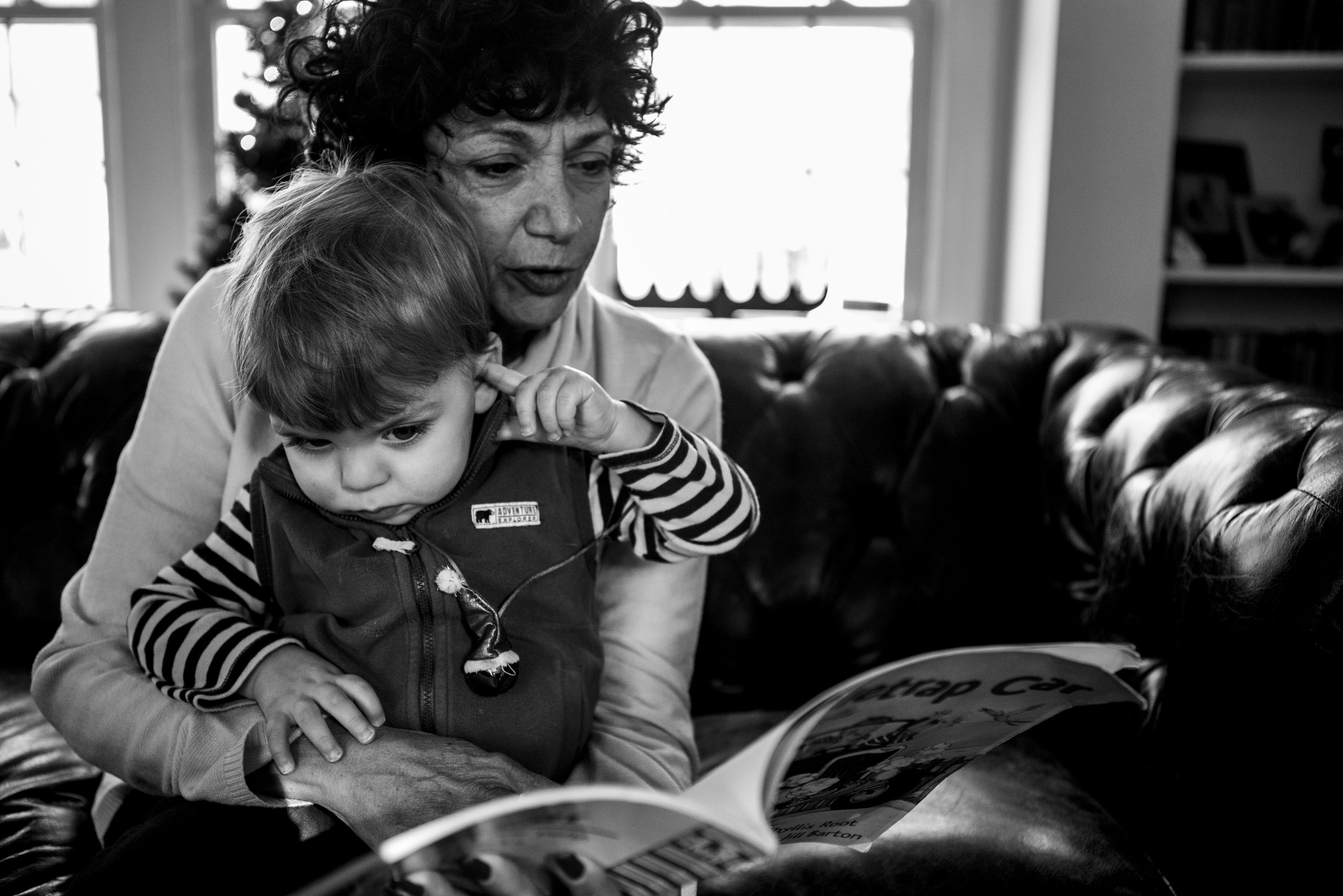 family pix by connecticut family photographer showing black and white picture of grandmother reading a book to toddler boy.