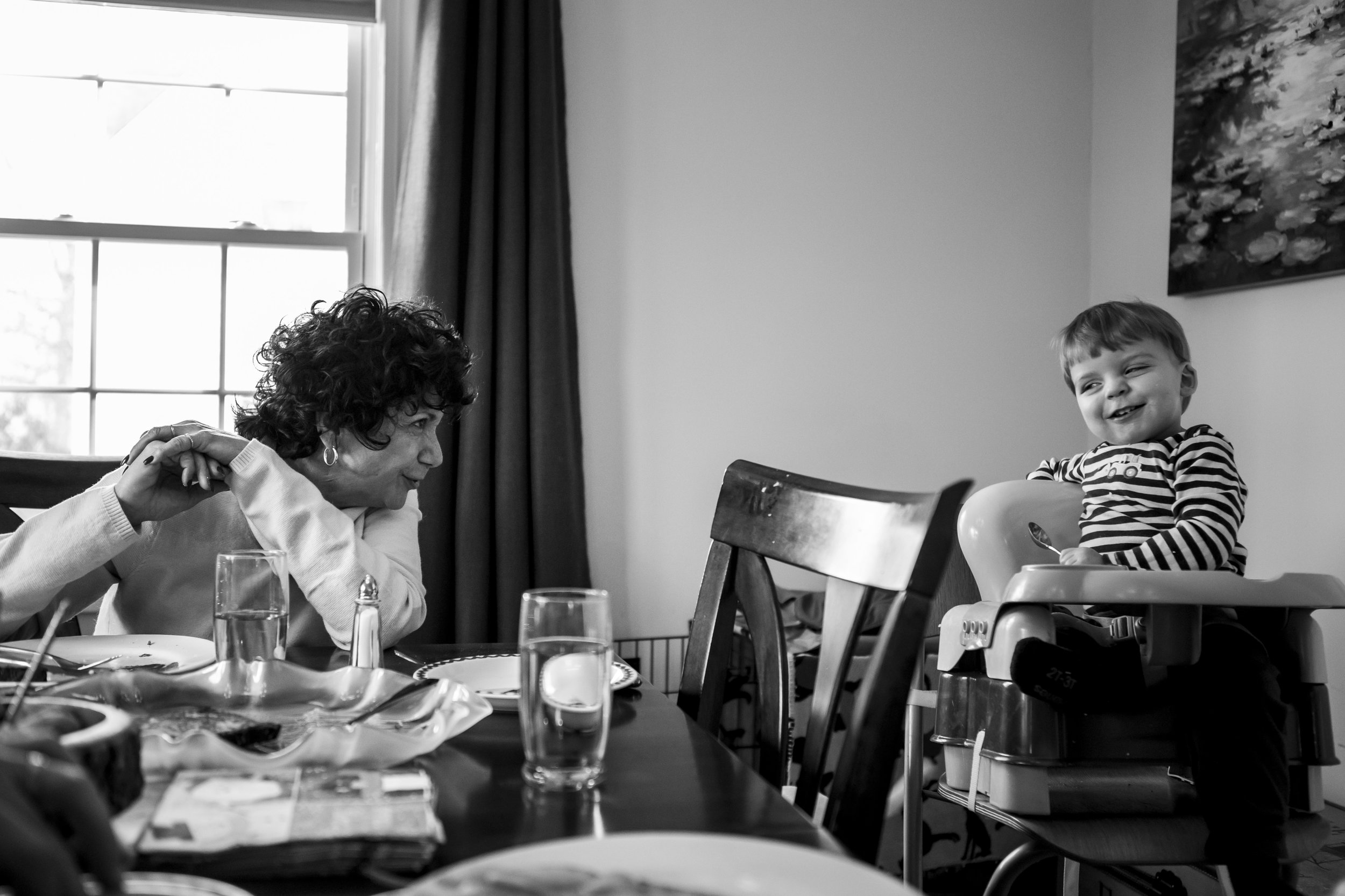 Connecticut photographer creates authentic family portraits in black and white, this candid image features grandmother and toddler striking at each other at the brunch table.