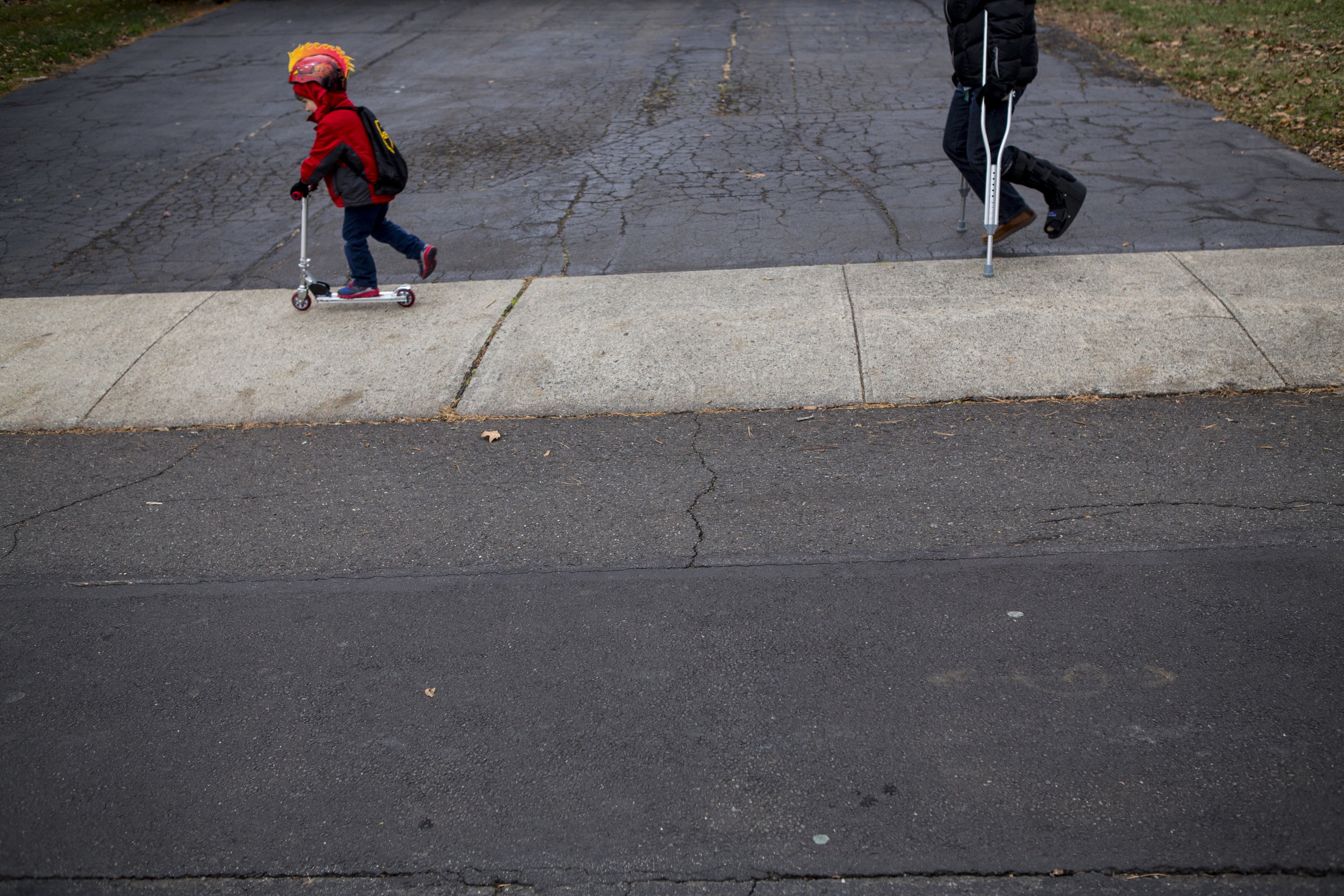 fine art child photography from Connecticut featuring minimalist composition with child dressed in red on a scooter, dad on crutches and lots of pavement.
