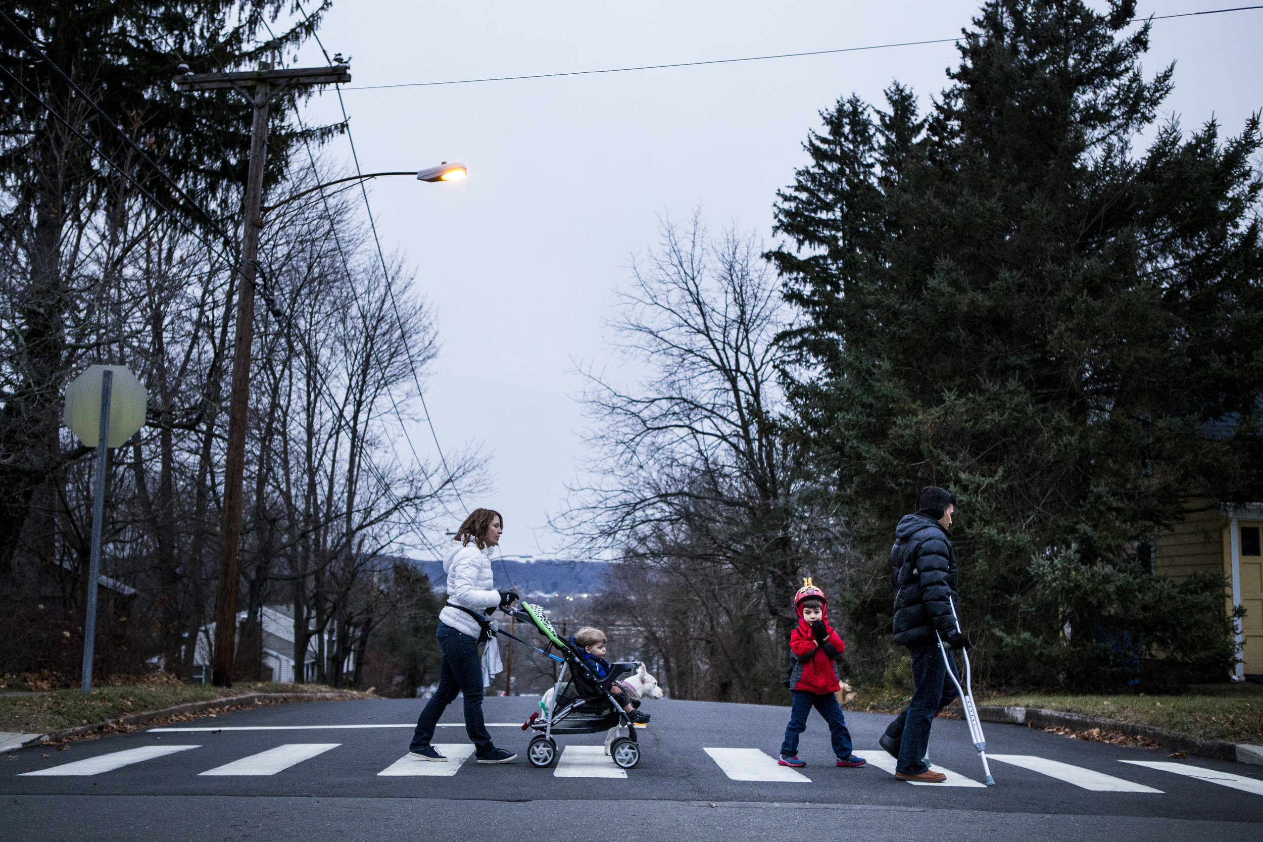 Real portraits for real families, candid family portrait of family of four crossing the street abbey road style picture of Connecticut family.