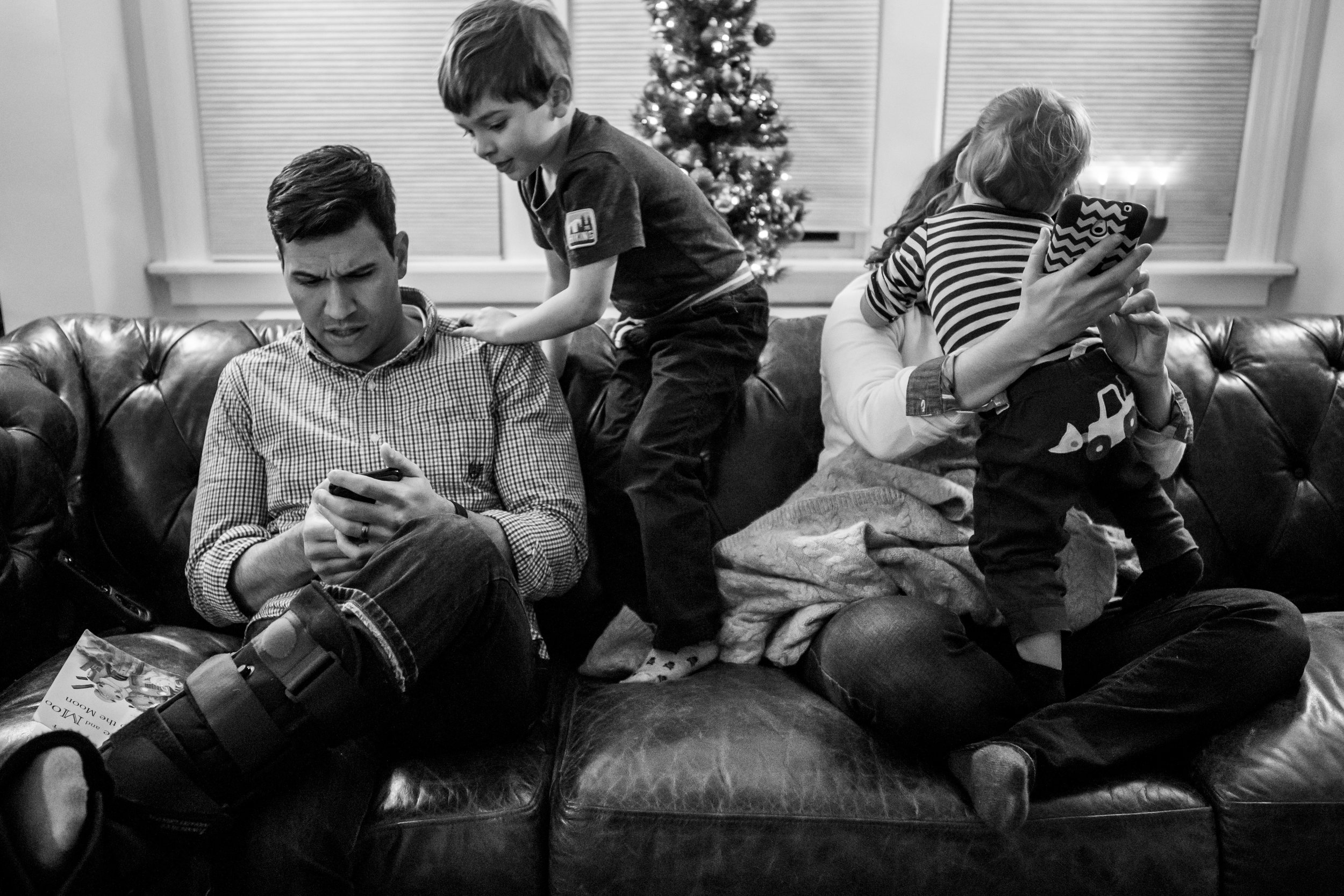Real life family portrait of Connecticut parents trying to use their smart phones while their children climb on them.
