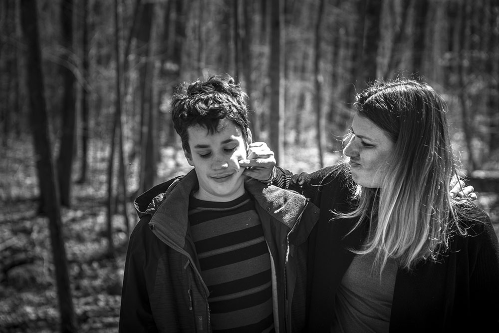 Candid portrait in black and white of mother and soon in the woods of Westbrook, Connecticut, documentary or lifestyle family portraiture.