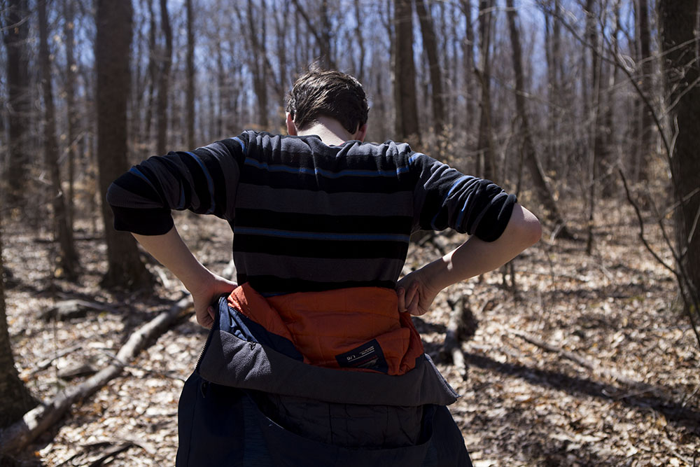 Teen tugs on clothes as he hikes through the woods in CT during candid, documentary, lifestyle family portraits.