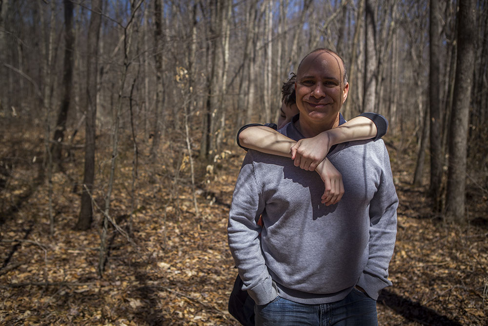 Lifestyle portraits in Connecticut (CT) of son hugging father in the woods.