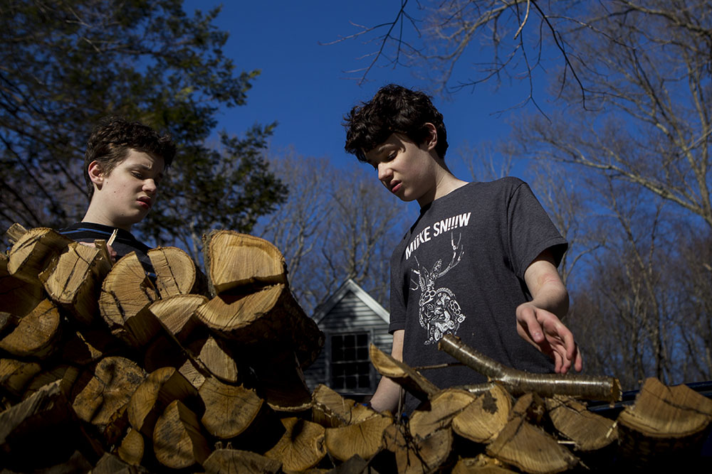 Family portraits in Connecticut featuring two teens stacking wood.