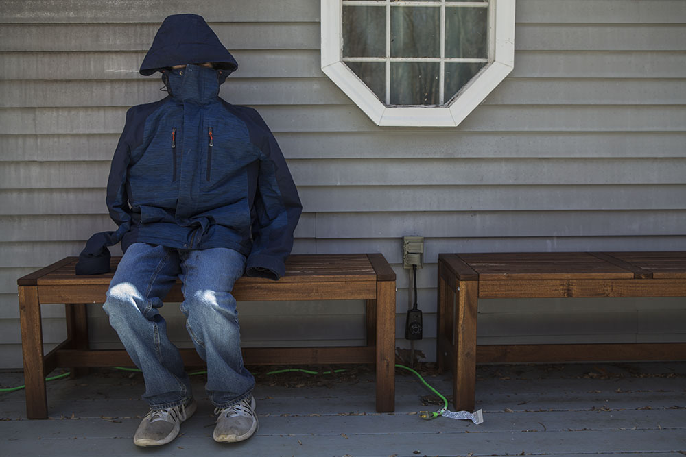 Authentic portrait in and alternative style of Connecticut child with hood covering his face, sitting outside his home.