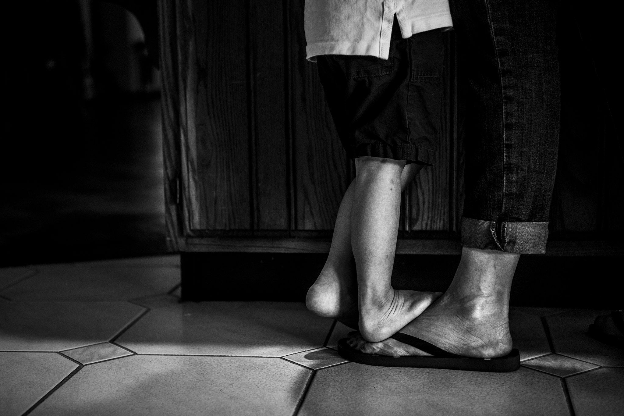 Fine art style image in black and white of ct boy mom featuring boys feet standing on mom's feet.