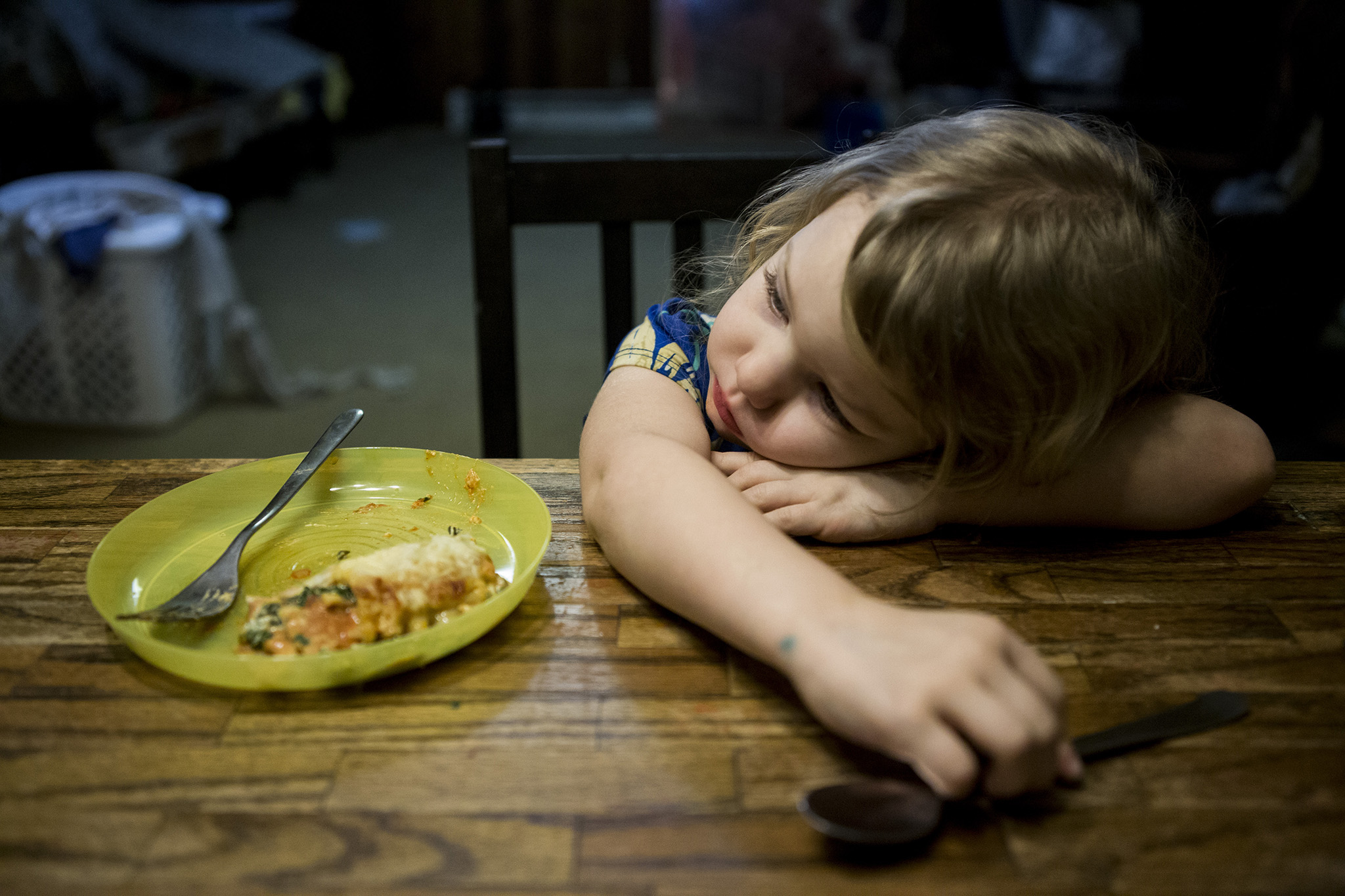 Real Life family pictures in Connecticut of a little girl who looks very tired laying her head on the dinner table with her half finished dinner sitting next to her.