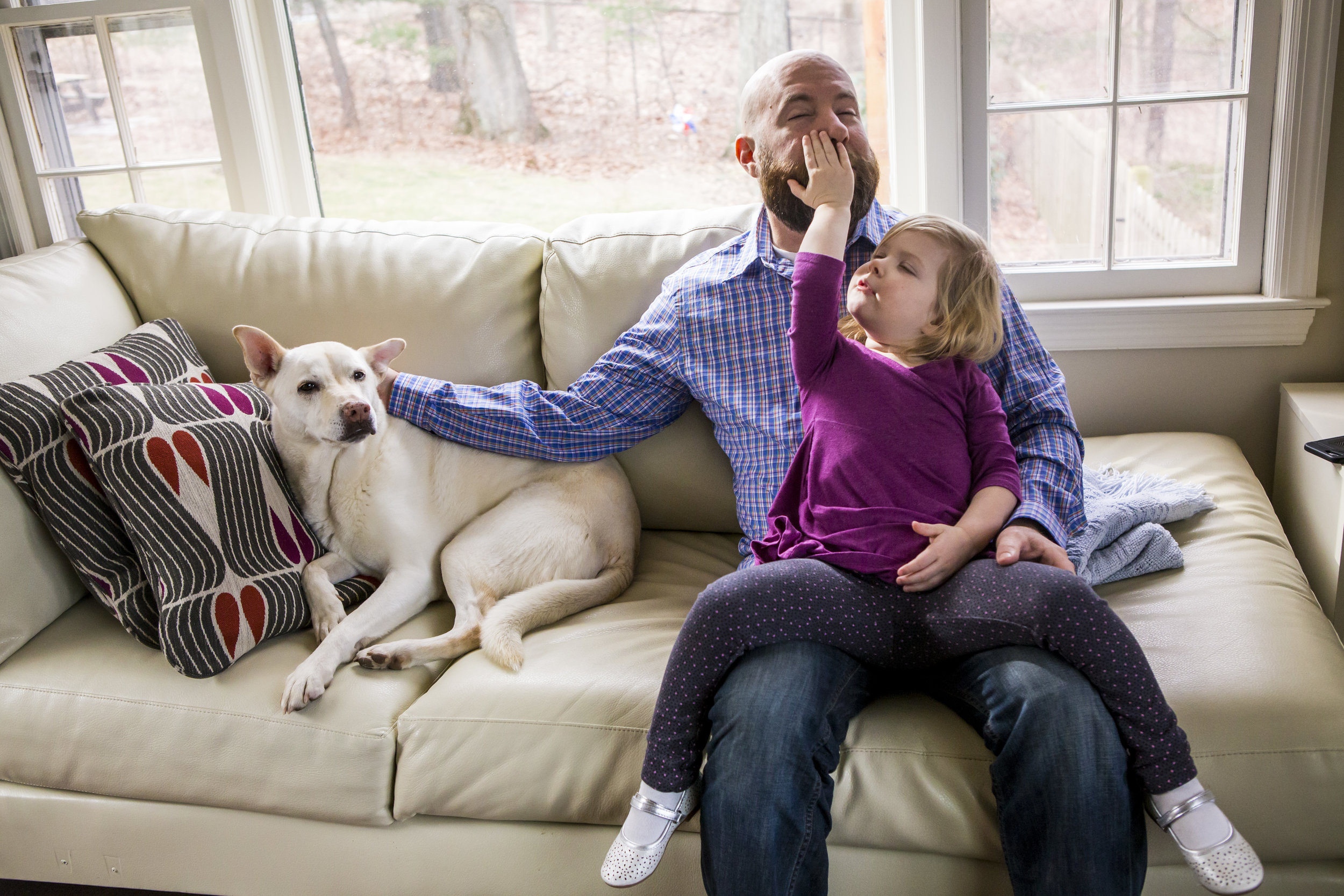 New haven family photo with girl, dad and dog on couch in front of window during in home family photography session.