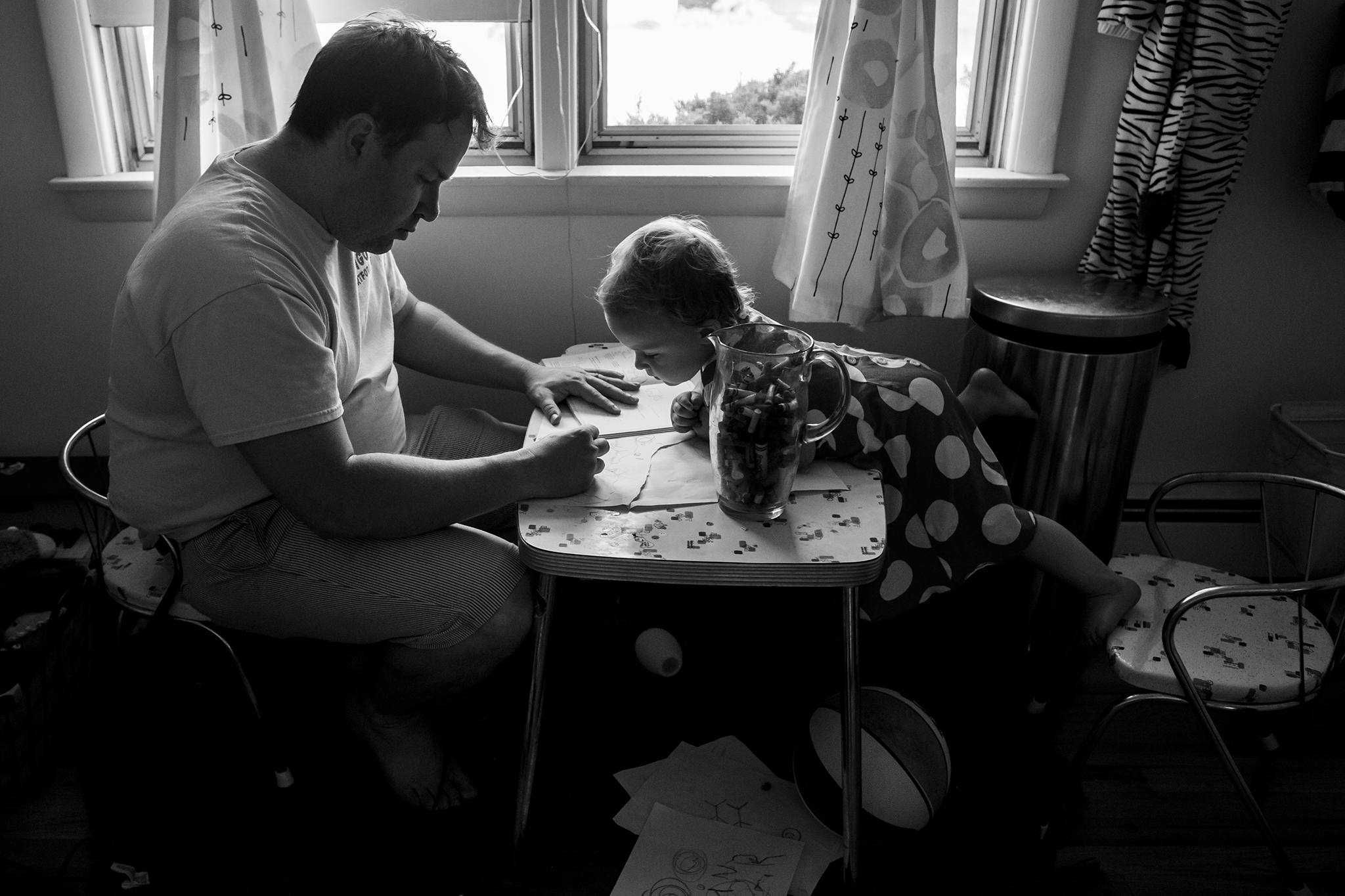 Connecticut family photography featuring father and daughter drawing in dramatic light and shown in black and white.