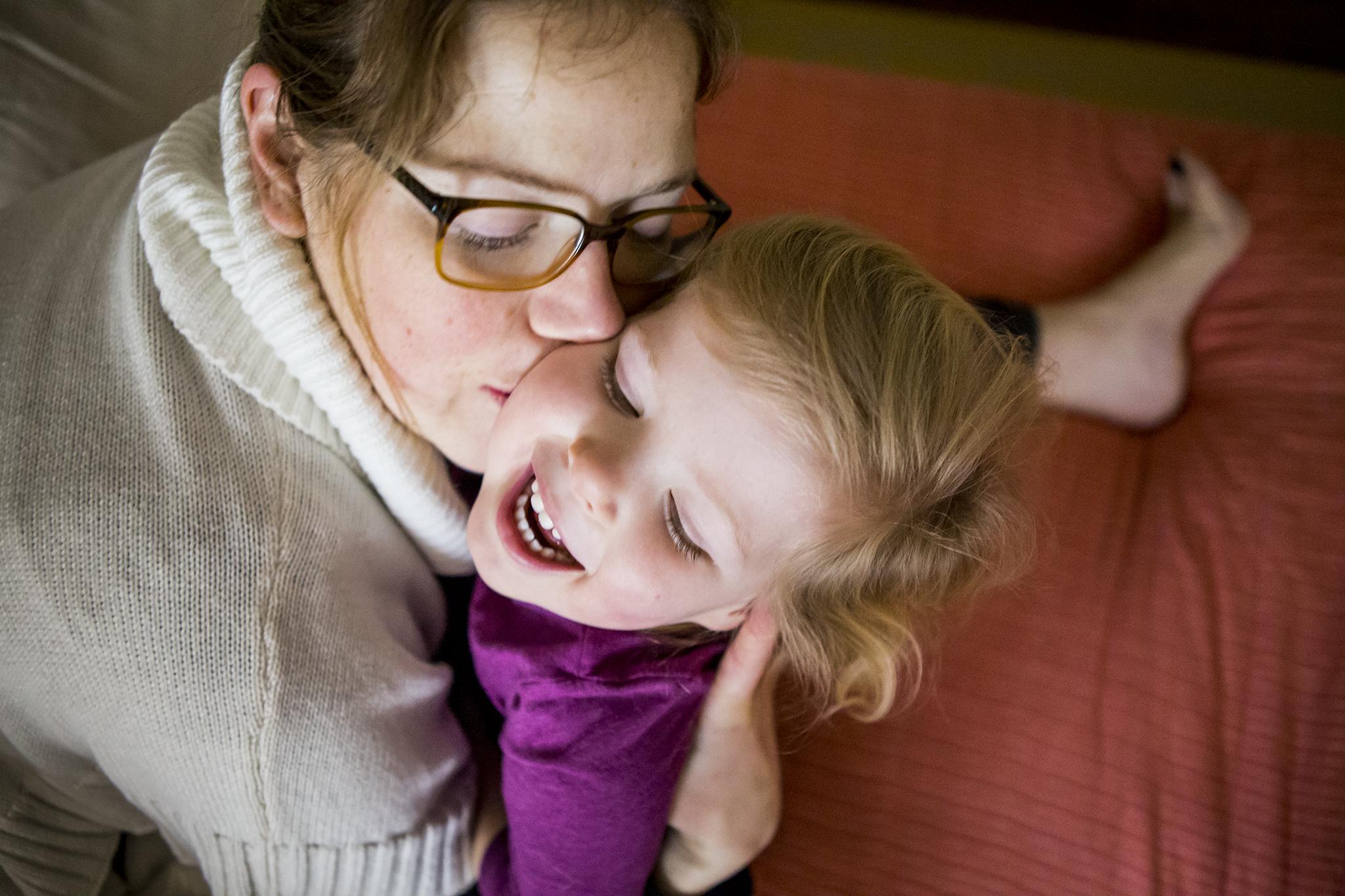 Joyful Connecticut family photos of mom hugging smiling daughter.