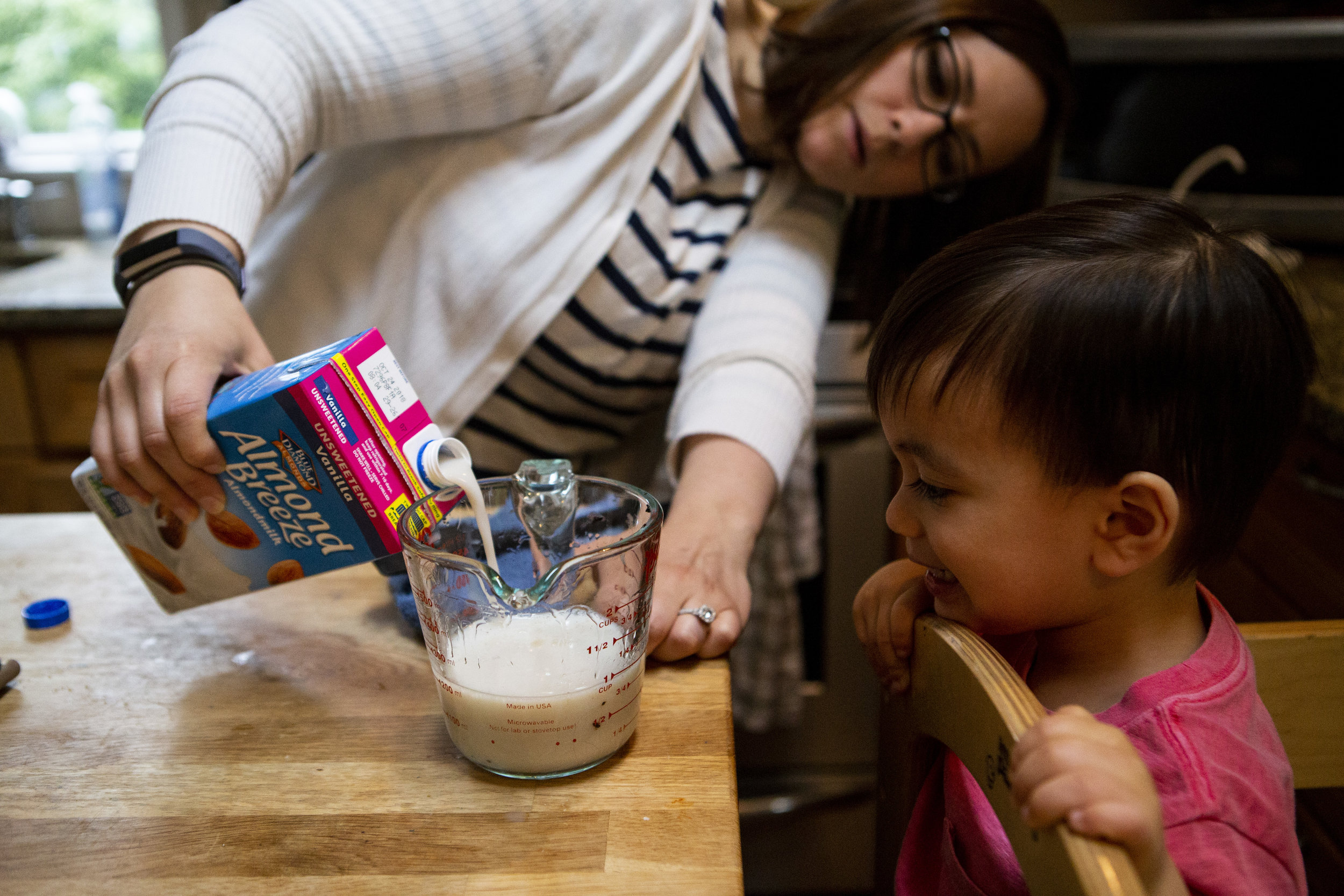 Boston mom measures almond milk with her son